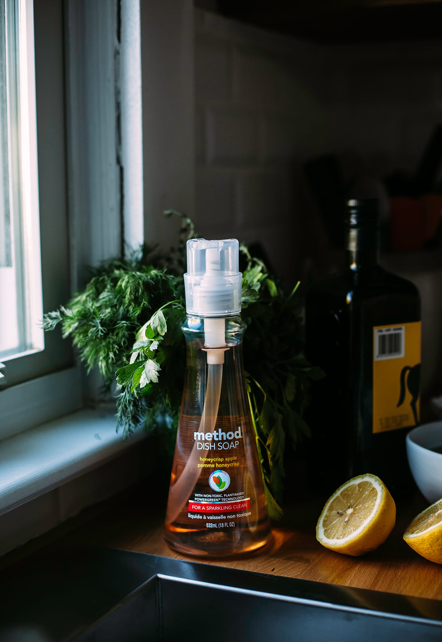 Image shows a bottle of dish soap by a kitchen sink.