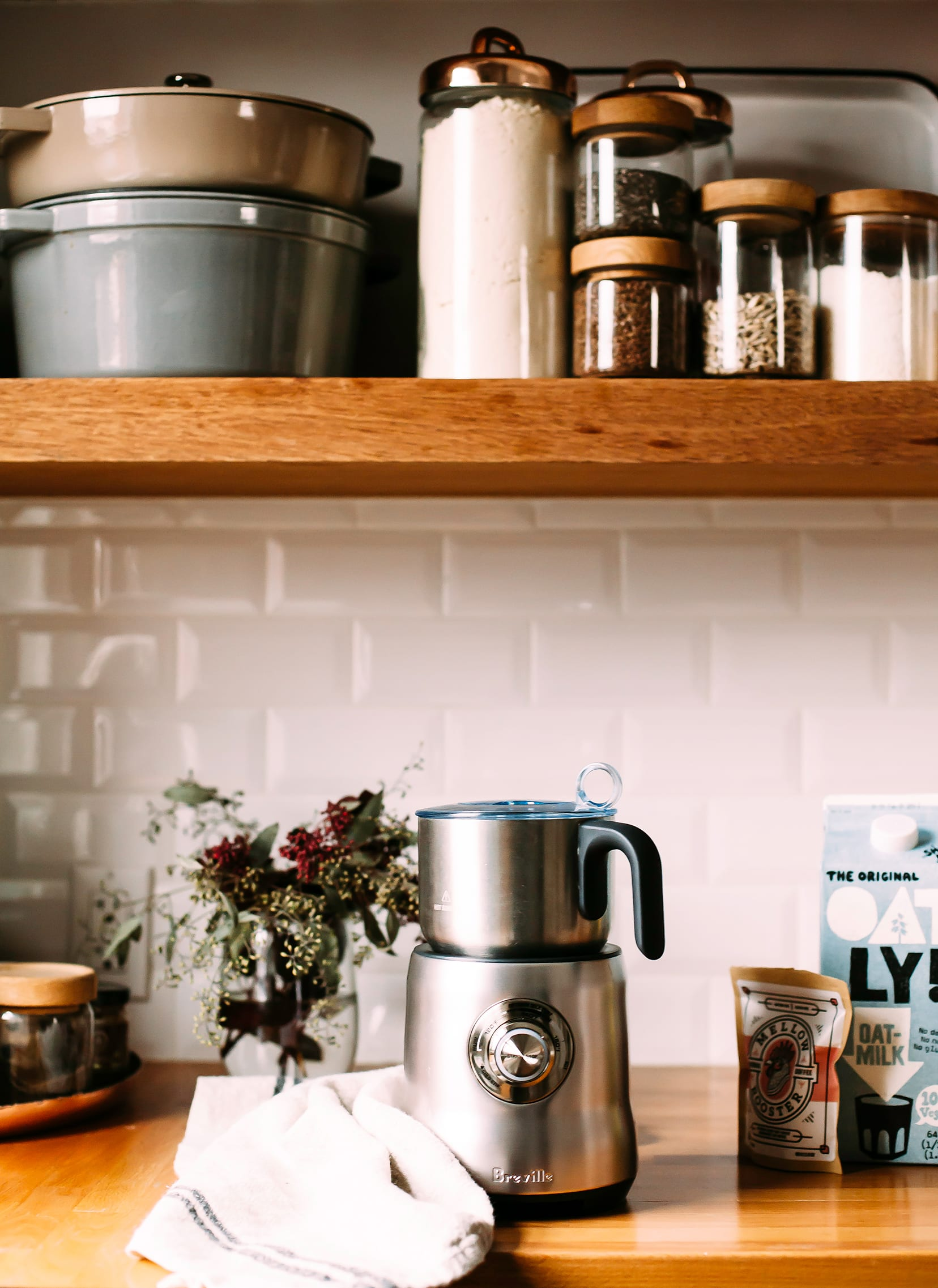 Image shows a kitchen counter scene with a milk frothier, a carton of oat milk, some eucalyptus branches in a jar, and open shelving against some white subway tile.