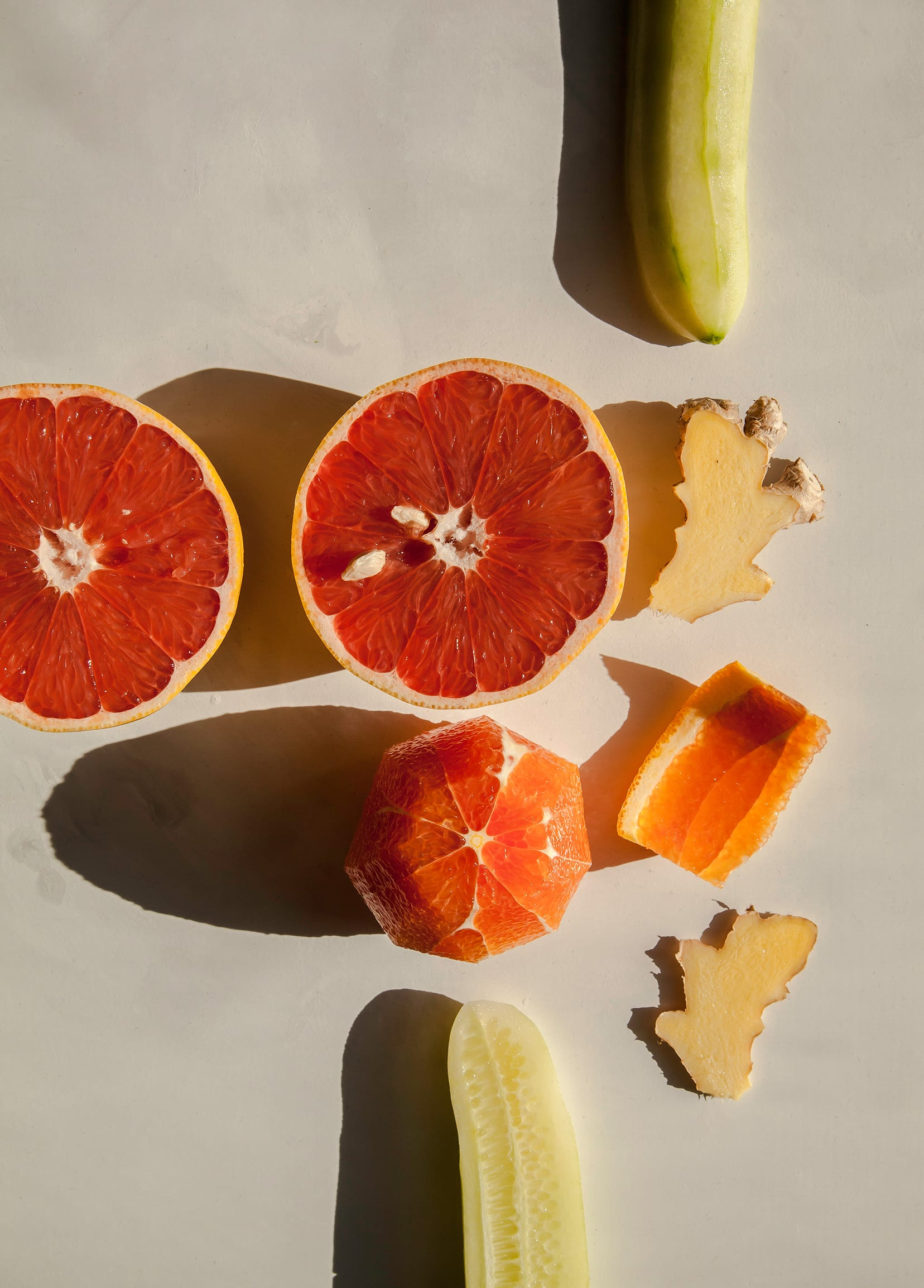 Over head shot of a halved grapefruit, peeled cucumber, orange, and sliced ginger in direct sunlight.
