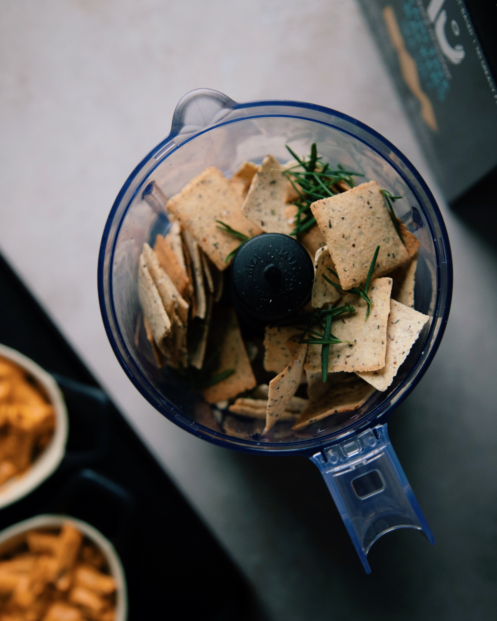 An overhead shot of grain-free crackers and rosemary in a mini food processor on a grey background.