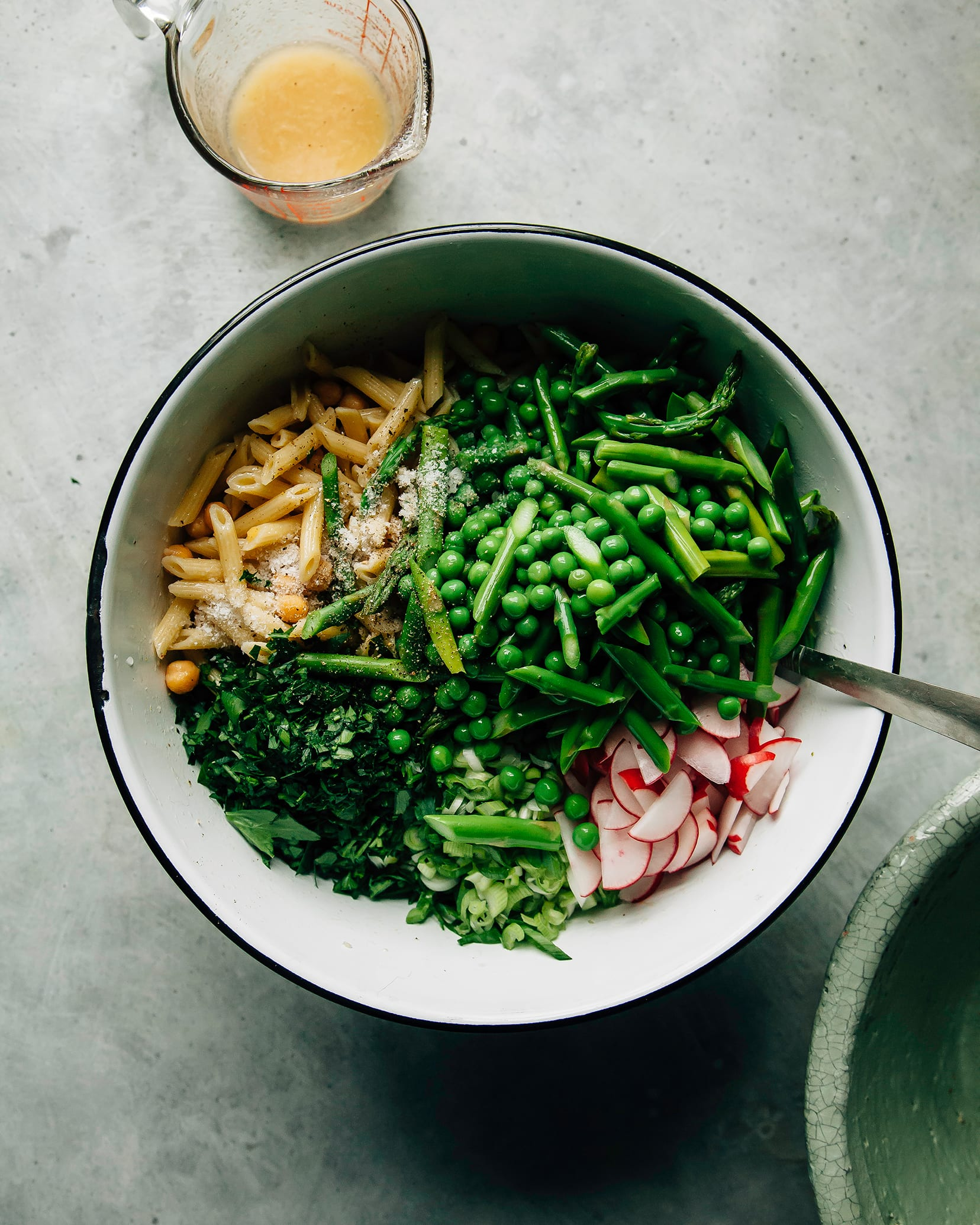 An overhead shot of a bunch of green vegetables, cooked pasta and chickpeas in a white bowl with a black rim. There is a glass measuring cup of vinaigrette nearby.