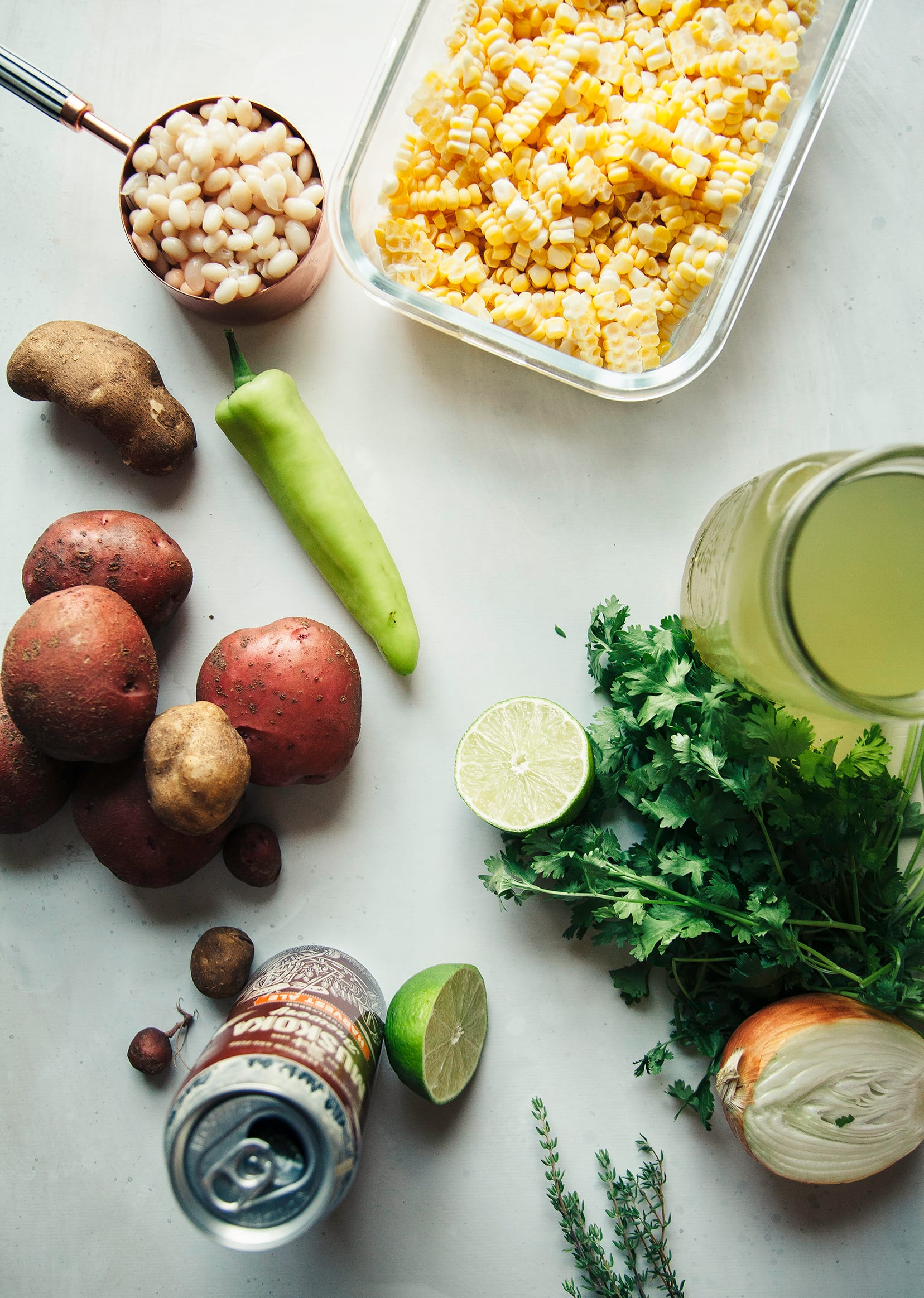 An overhead shot of prep for a vegan corn chowder on a white background.