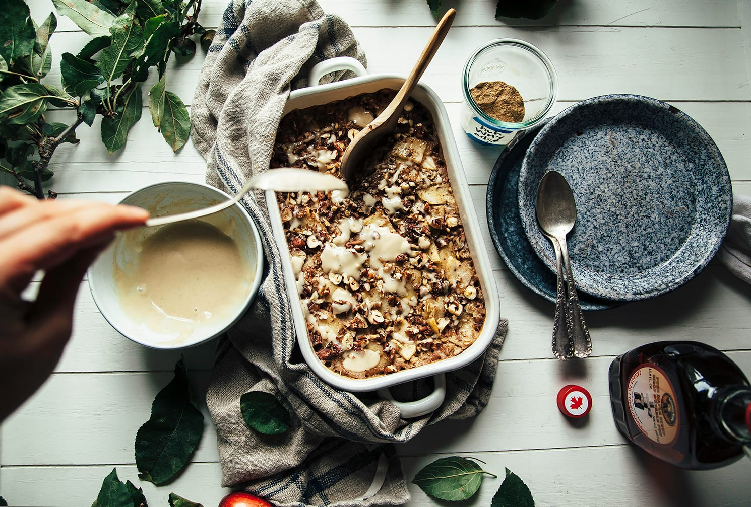 A hand is drizzling a creamy sauce over a dish of baked oatmeal that is topped with cooked apples and nuts.