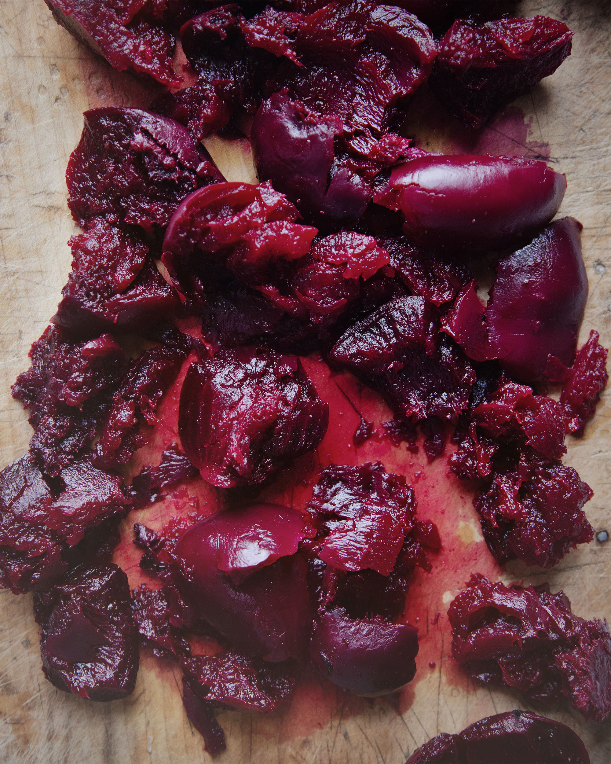 "An overhead shot of cooked beets that have been ""crushed"" on a cutting board."