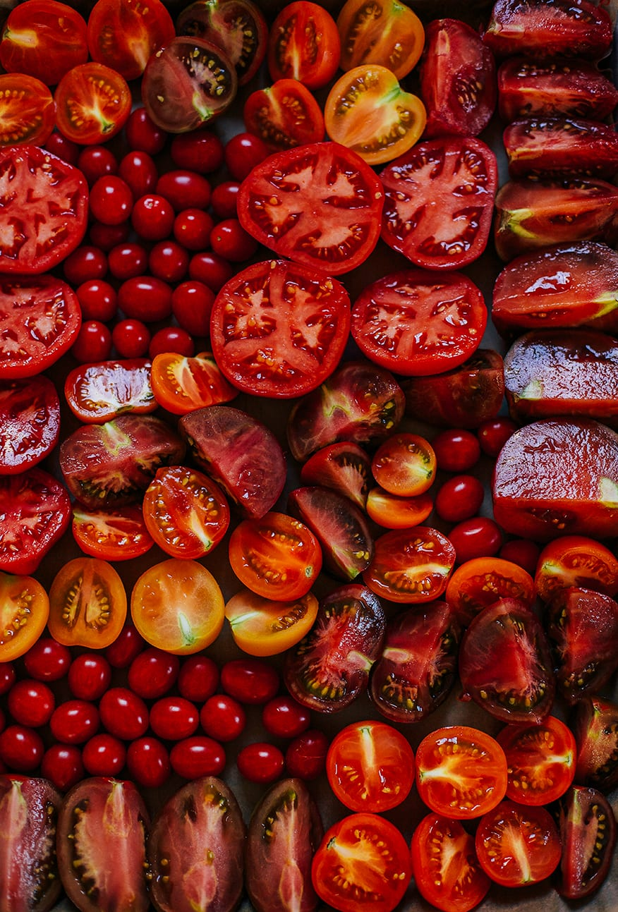 An overhead shot of a bunch of cut heirloom tomatoes on a sheet pan, just before being roasted.