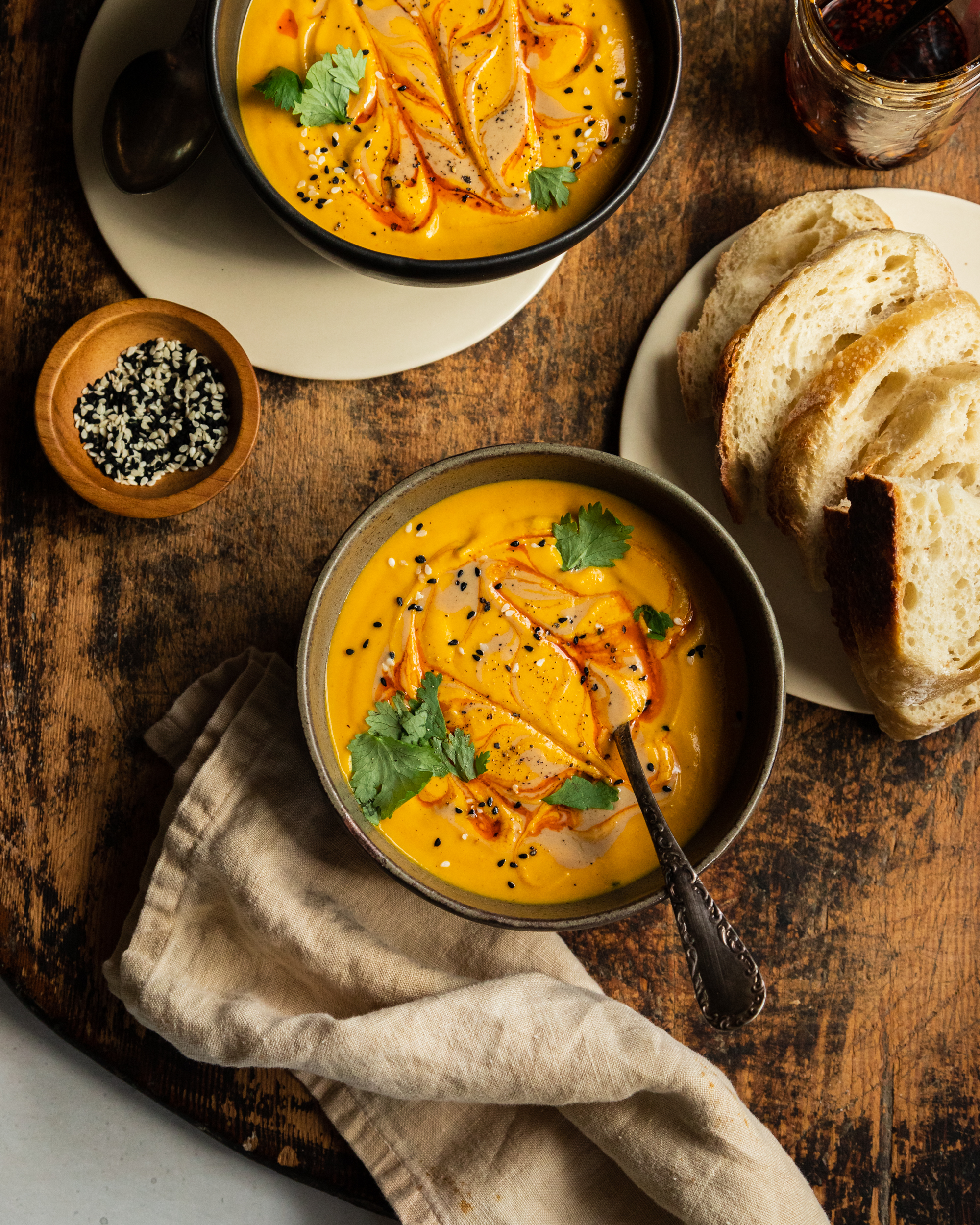 An overhead shot of a bowl of vibrant and creamy orange soup that is swirled with a red slick of oil on top. The soup has a crust of bread in it and is also garnished with sesame seeds and cilantro.