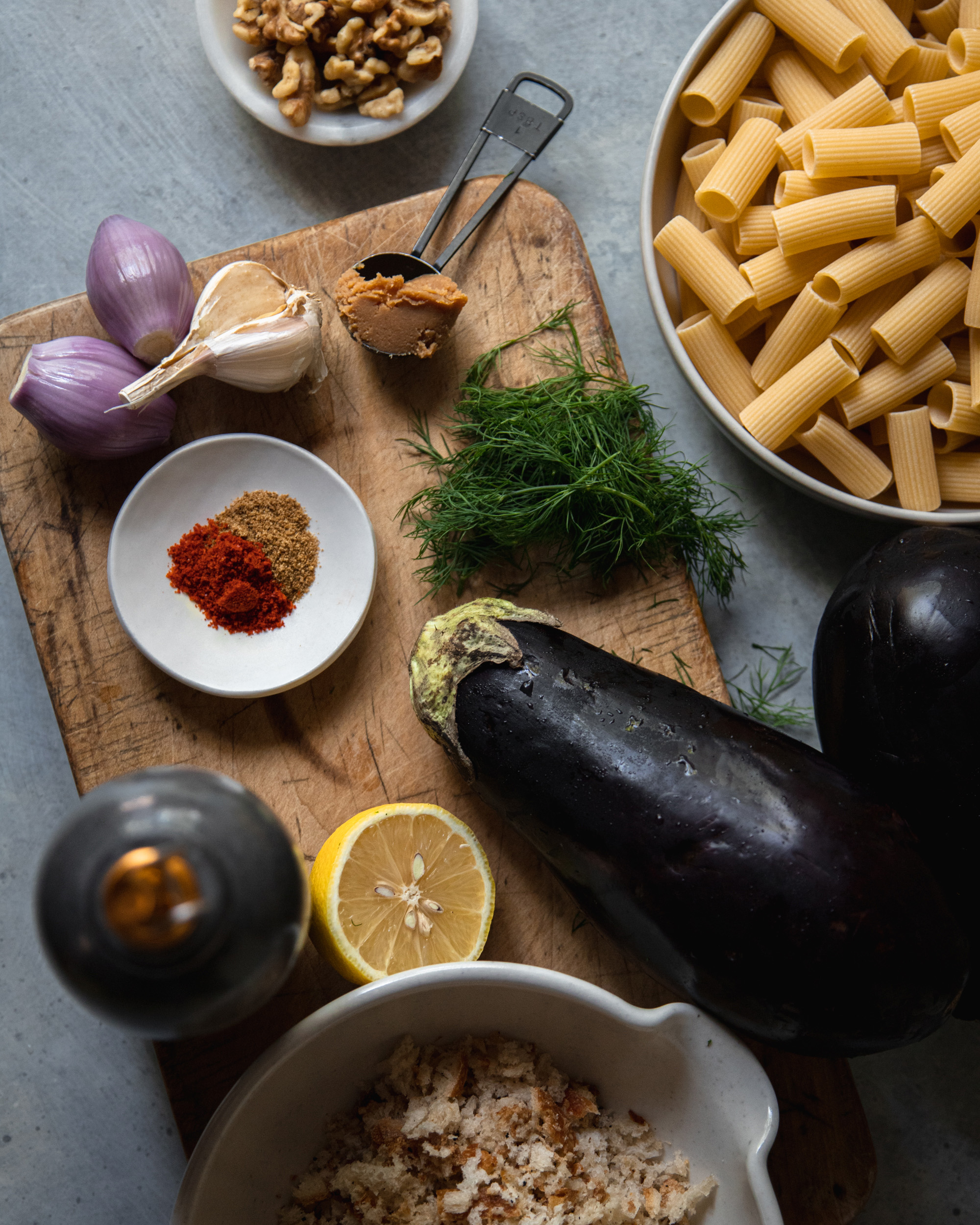 An overhead shot of ingredients for a creamy eggplant pasta on a grey-ish blue background.