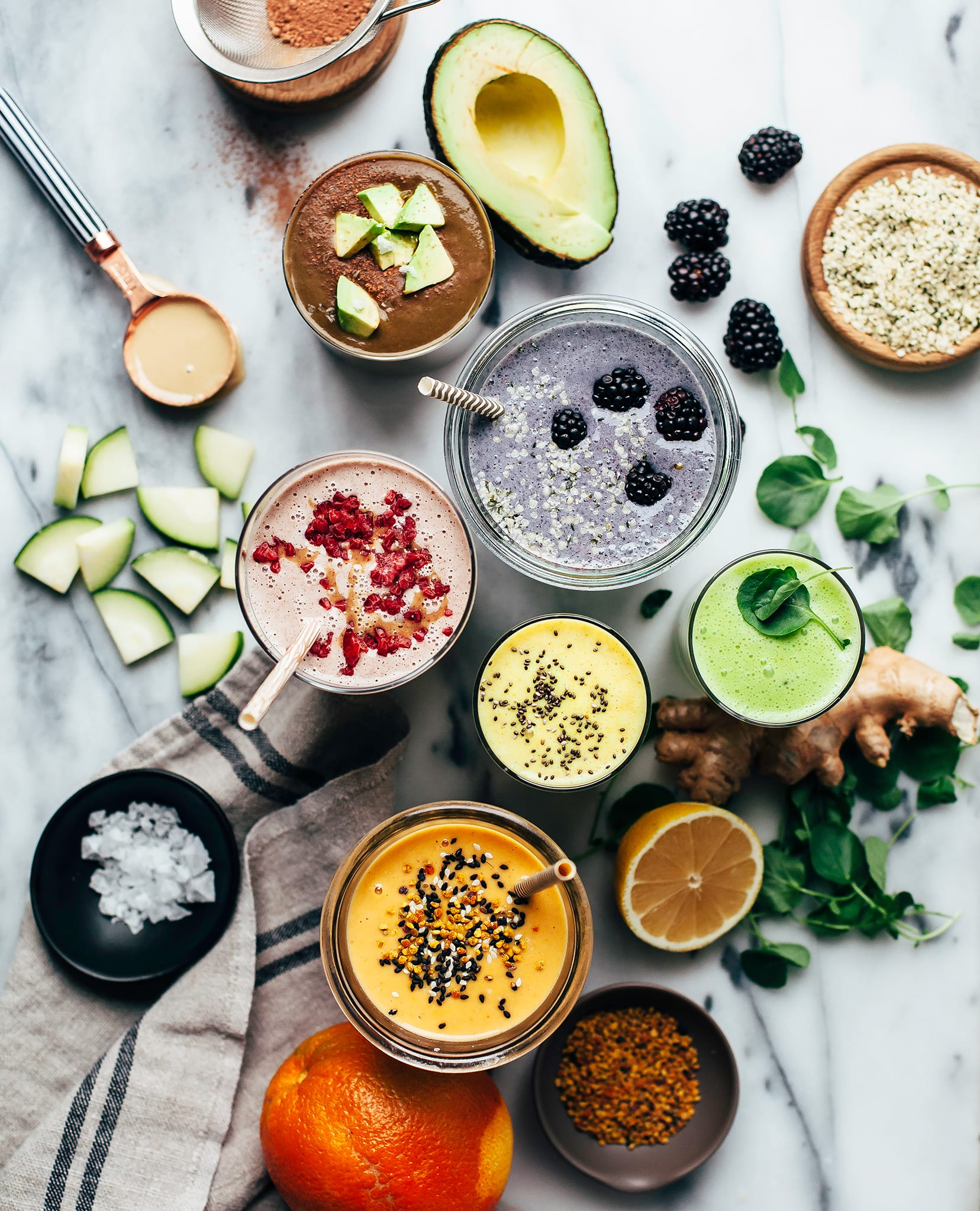 An overhead shot of some healthy vegan smoothies on a marble background. Ingredients are arranged around the smoothies, along with a beige tea towel.