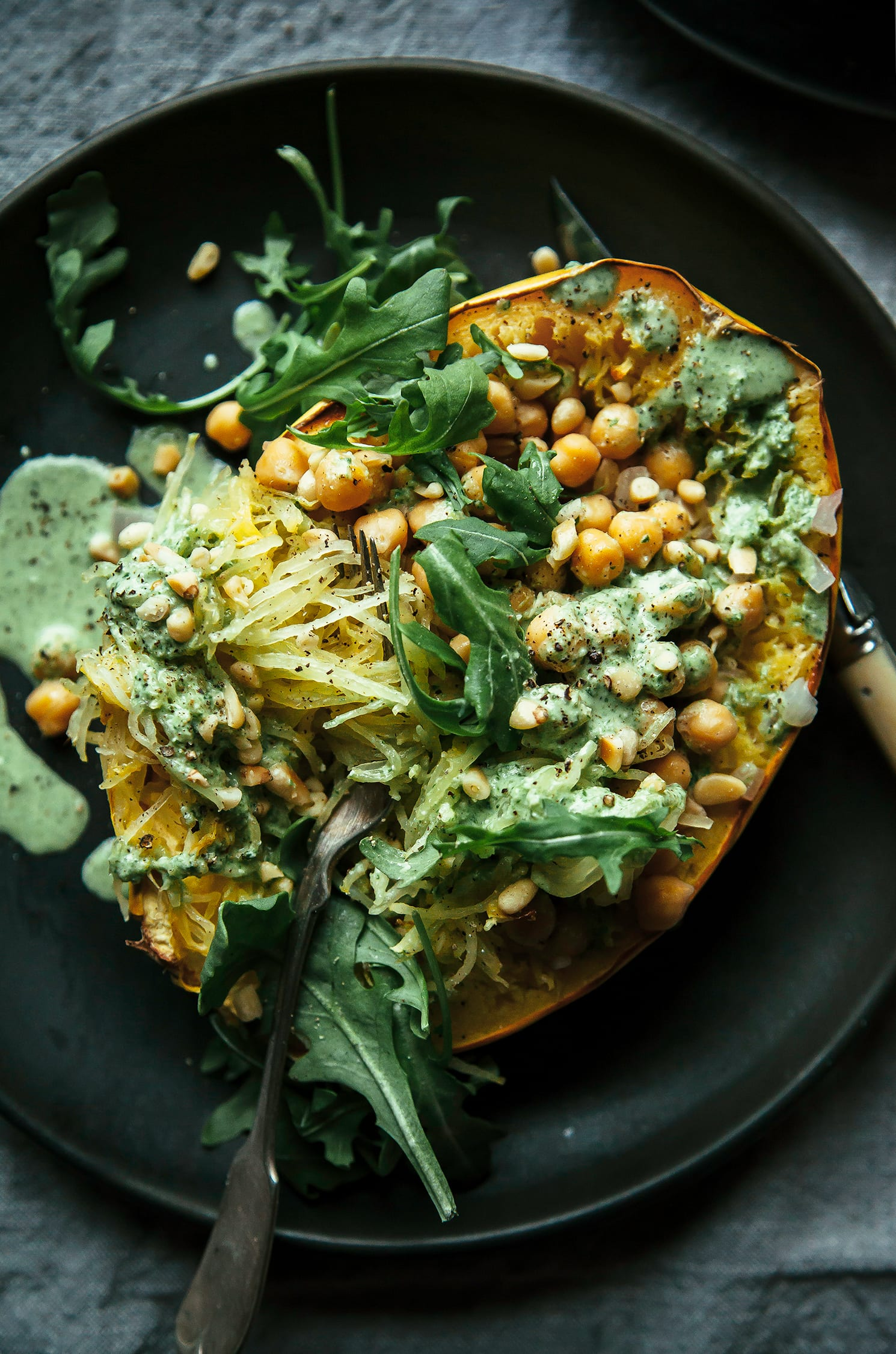 An overhead shot of a stuffed spaghetti squash half on top of a matte black plate that's set on top of a grey linen tablecloth. Inside the spaghetti squash is chickpeas, bright green garlicky arugula cream and leaves of arugula as well.