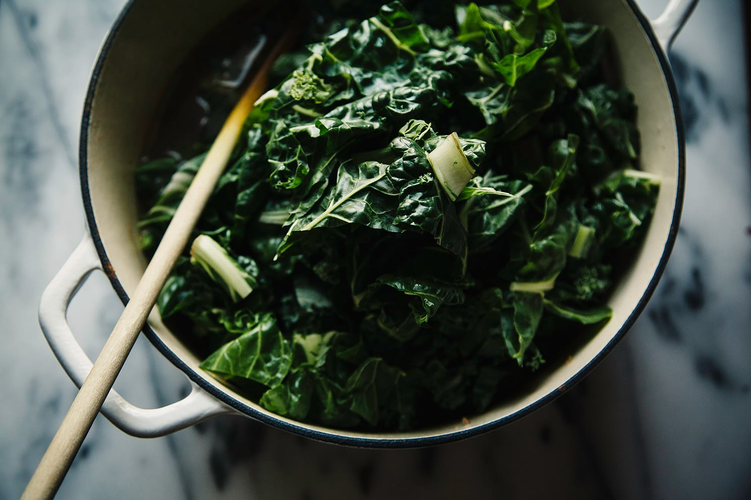 A white Dutch oven with tons of chopped chard added to it. A wooden spoon is sticking out of the pot.