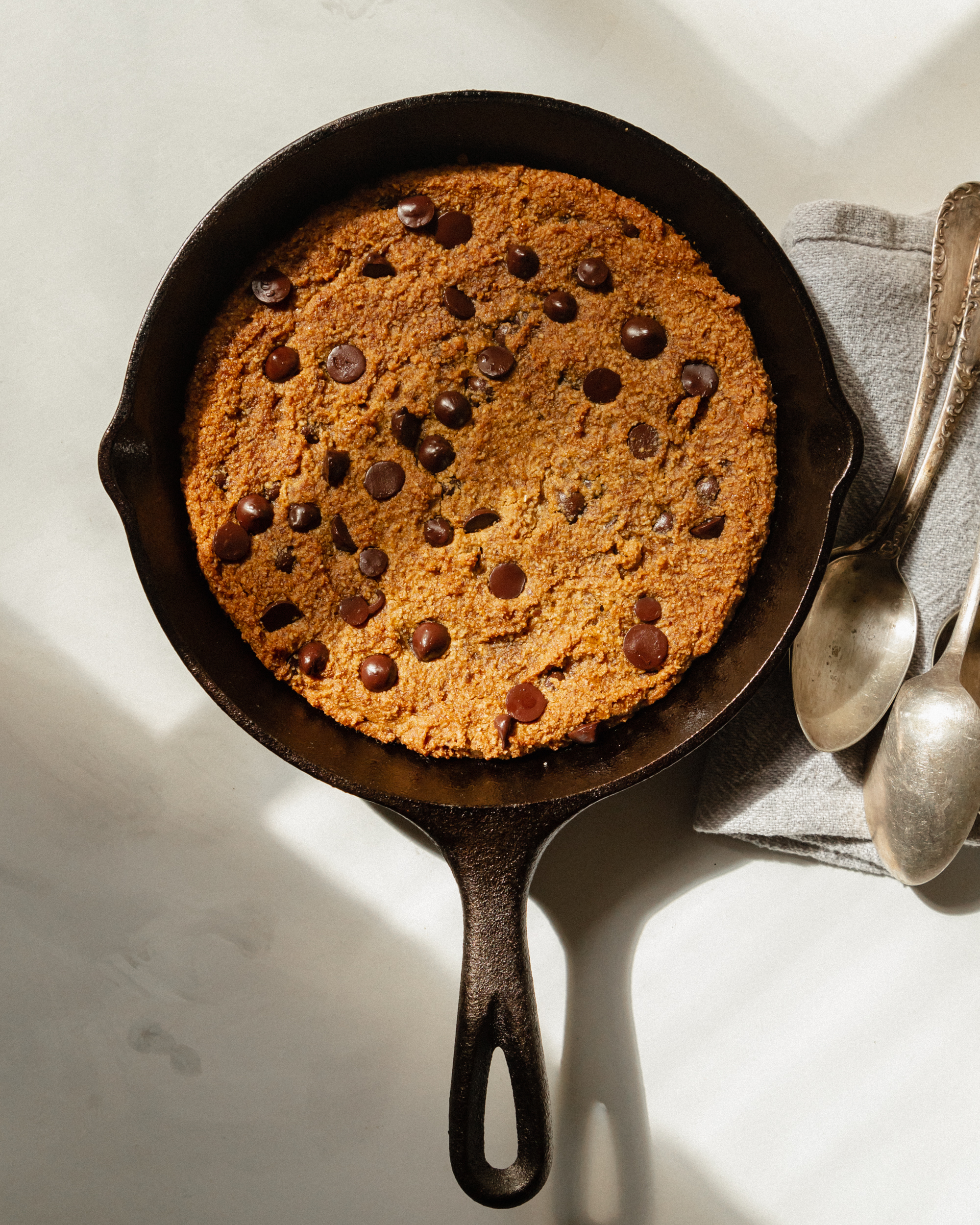 An overhead shot of a large cookie that has been baked in a skillet. There is a grey napkin with a few spoons on top nearby.
