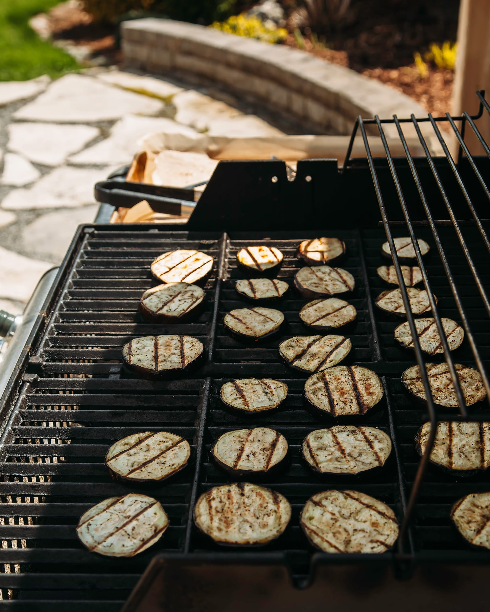 Side angle photograph of eggplant slices on an outdoor grill with a garden in the background.