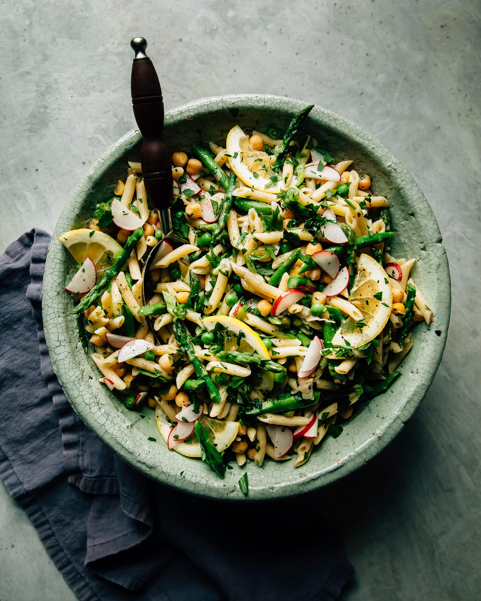 An overhead shot of a pasta salad with lots of green vegetables and herbs in a sage-green ceramic bowl.