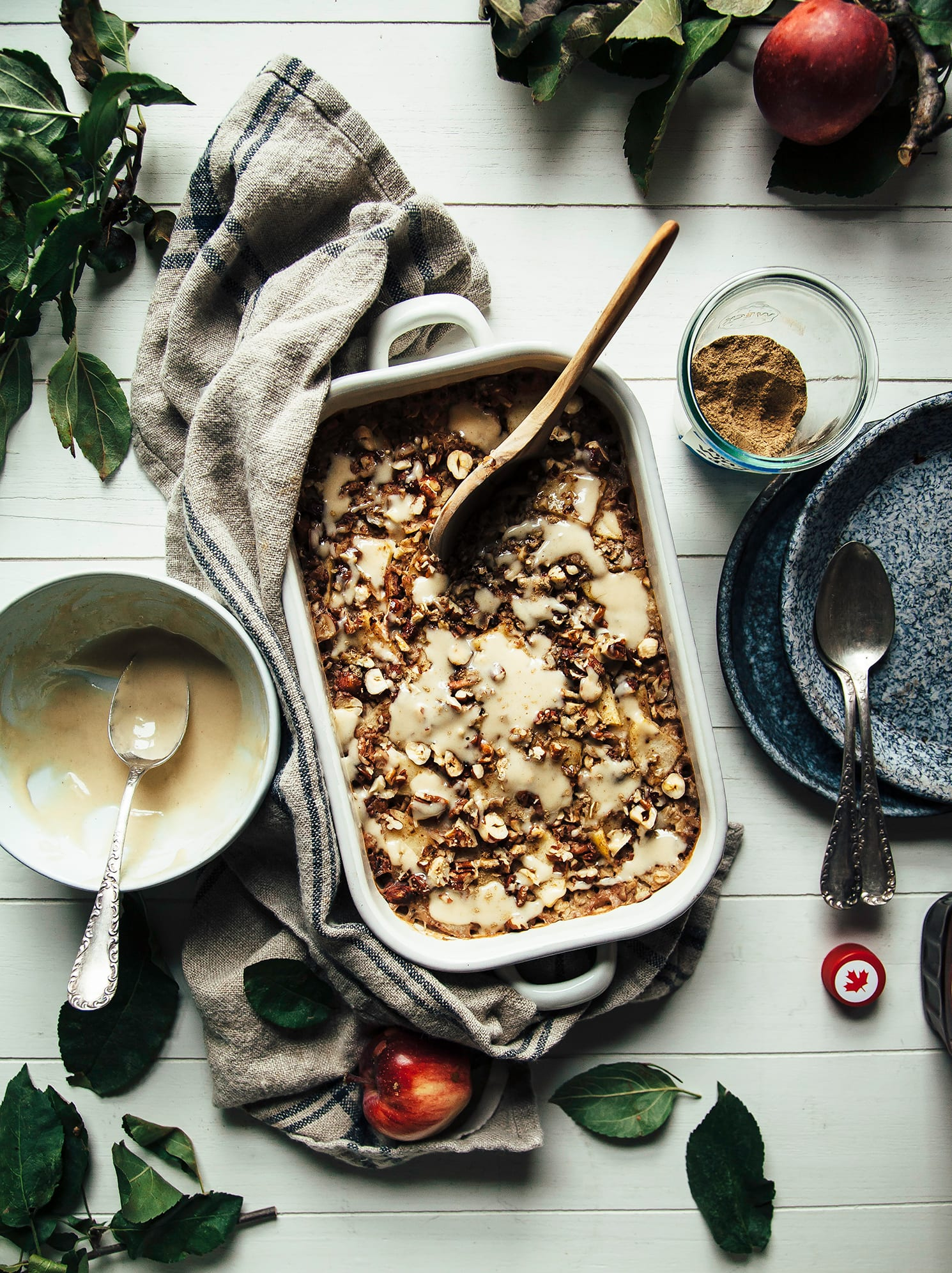 An overhead shot of baked oatmeal that is topped with cooked apples and nuts. A bowl of creamy sauce is seen to the side.