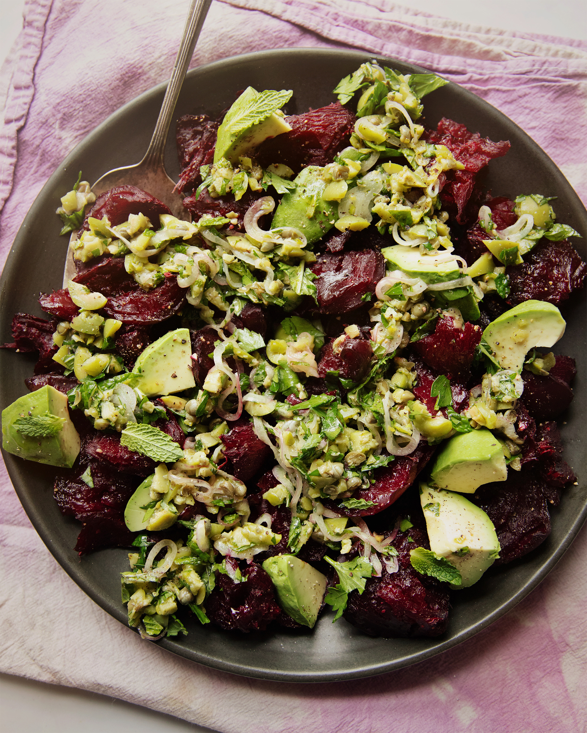 An overhead shot of a crushed beets salad with chunky olive dressing, mint, and avocado. The salad is on a matte black plate on top of a pink and purple tie-dyed linen.