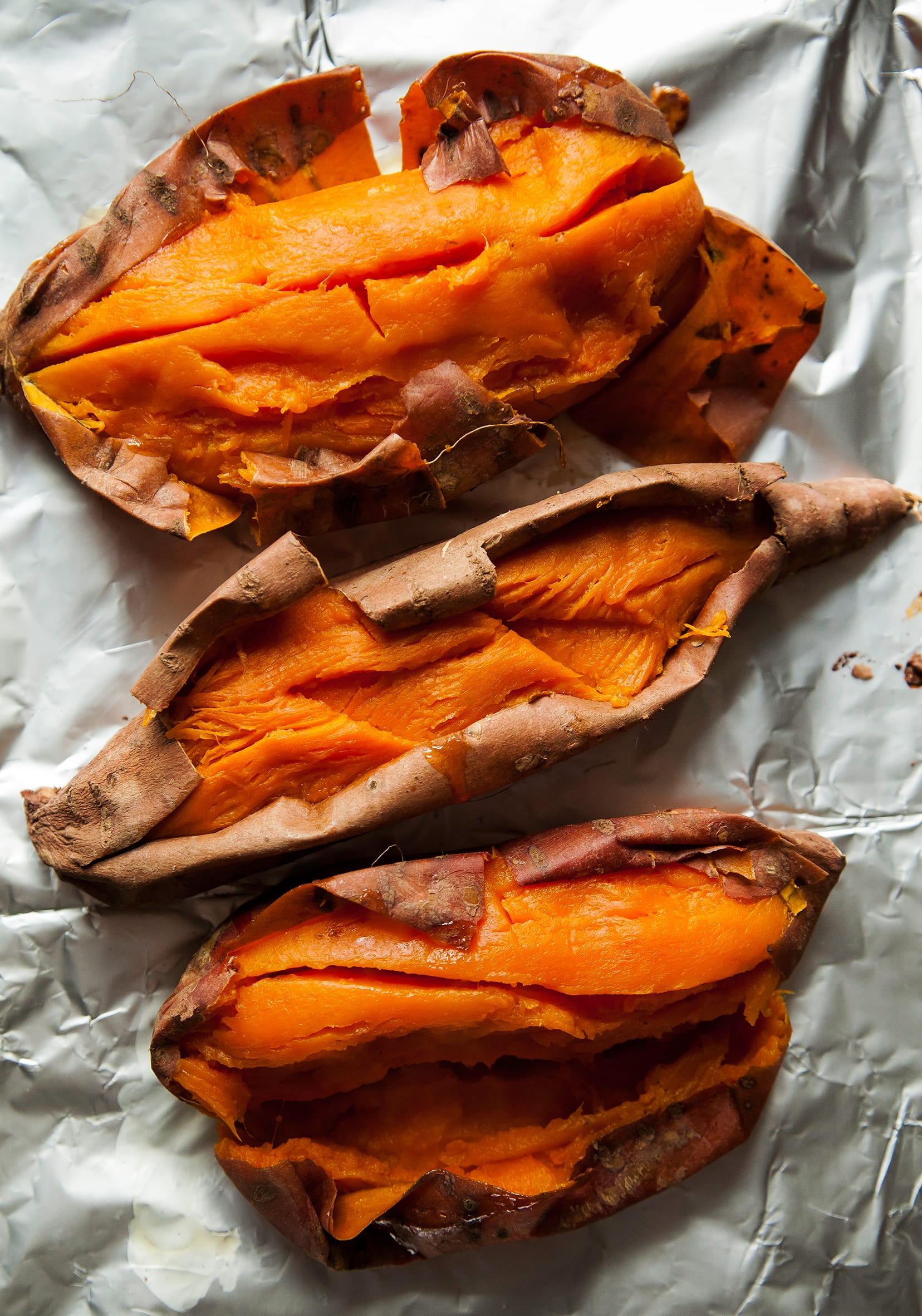 An overhead shot of roasted and split open sweet potatoes on top of foil.