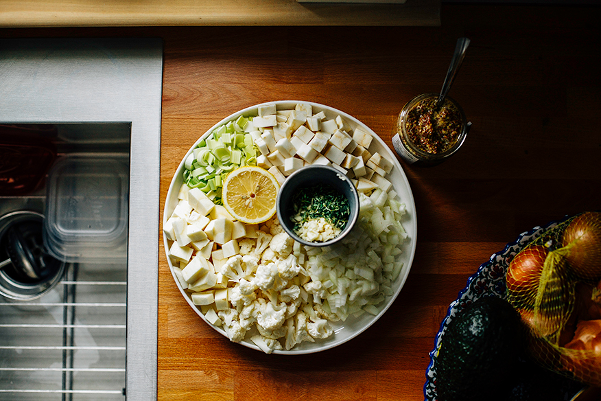 An overhead shot of chopped winter vegetables, all arranged on a white plate on top of a butcher block countertop.