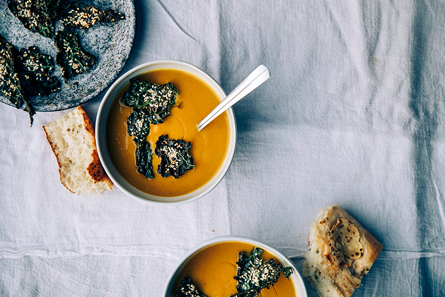 An overhead shot of kabocha squash and chestnut soup, garnished with crispy kale chips. There are two bowls of the light orange soup on a white linen background. Ripped pieces of bread are placed to the side.