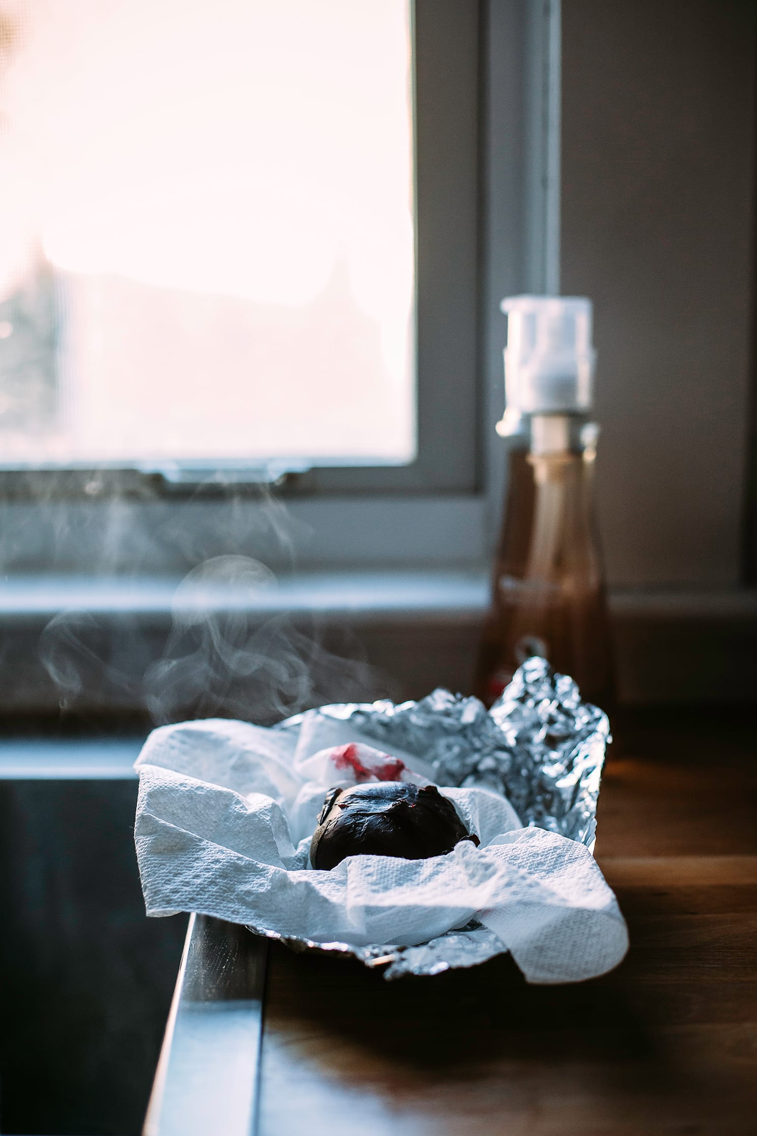 Image shows a freshly roasted beet on a kitchen counter, wrapped partially in foil and steaming.