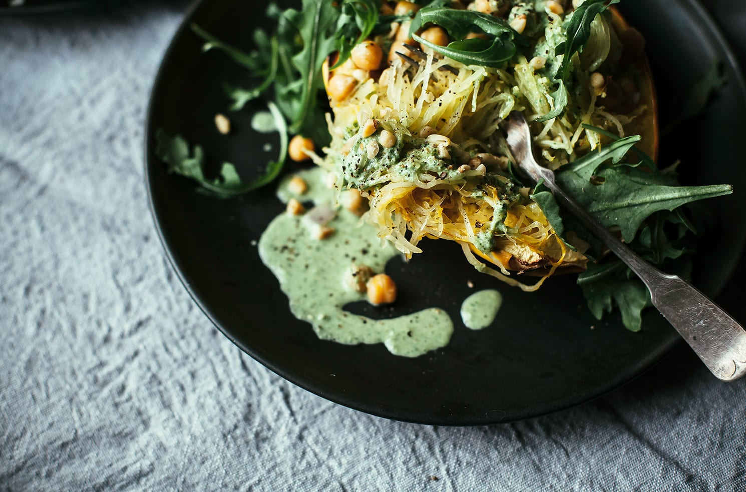 An overhead shot of stuffed spaghetti squash with a bright green arugula cream, leaves of arugula, and chickpeas. The squash is served on a black plate on top of a grey linen tablecloth.