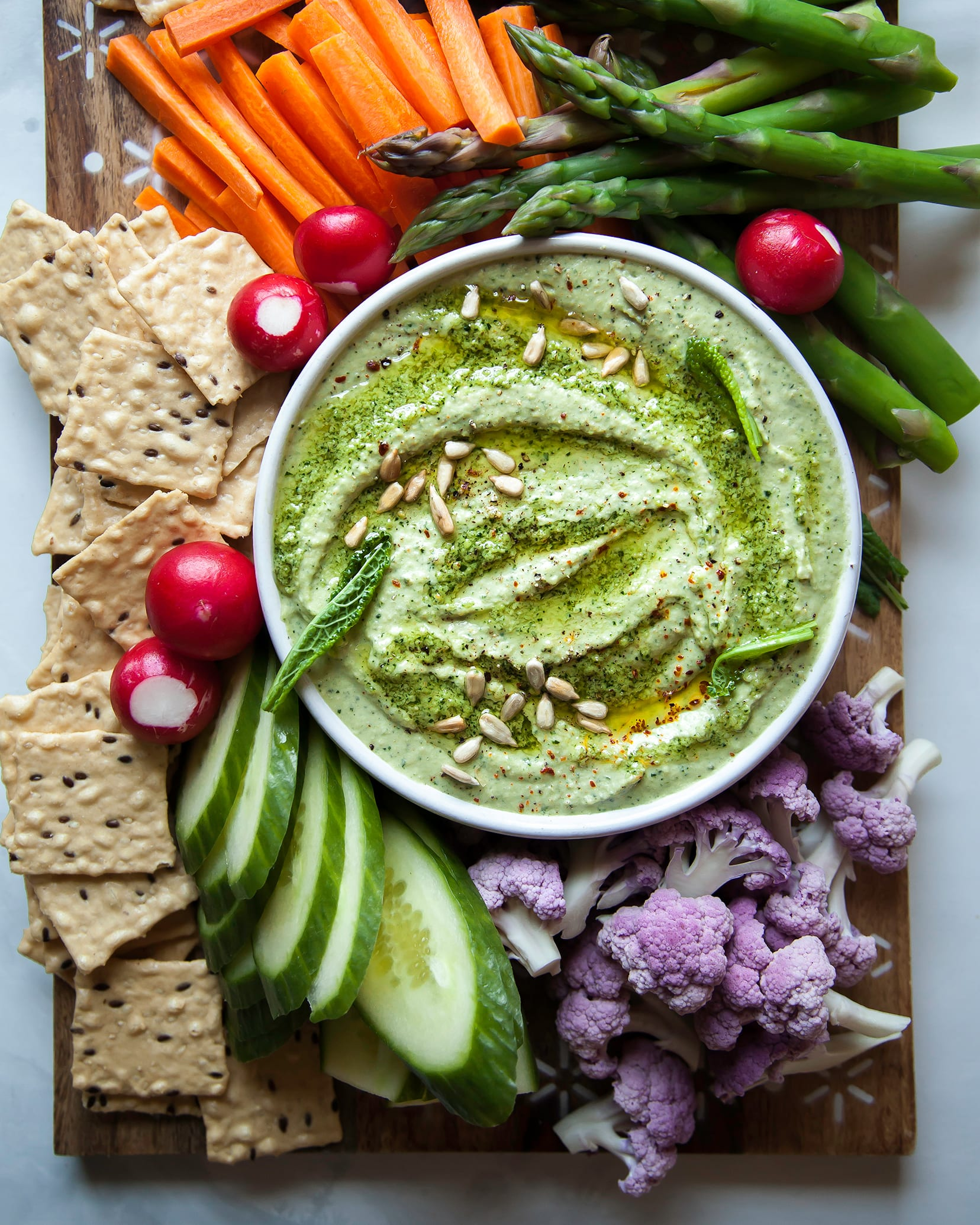 An overhead shot of a creamy light green dip with vegetables served alongside.