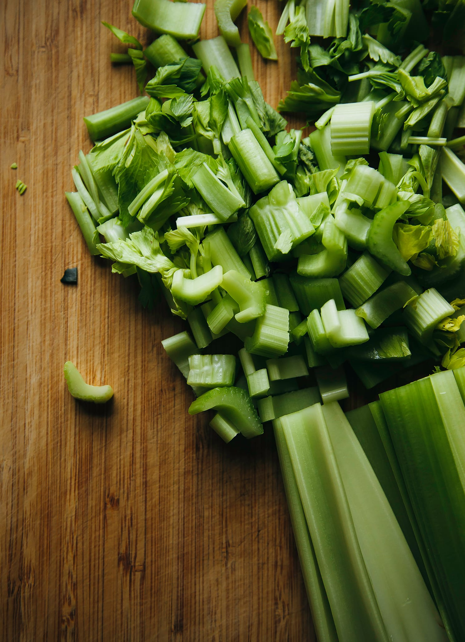 Up close shot of chopped celery on a bamboo cutting board