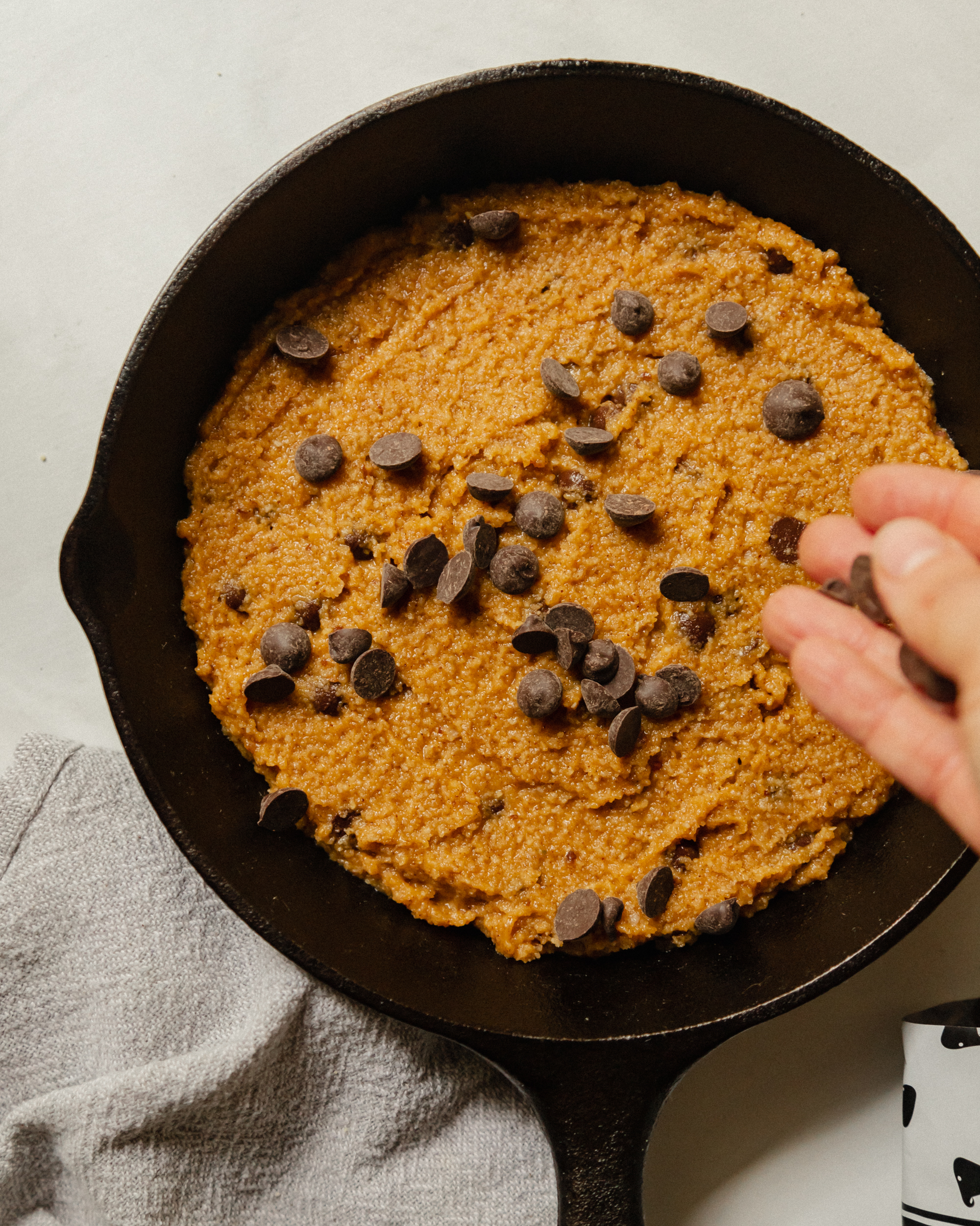 A hand is seen sprinkling chocolate chips on top of a large portion of cookie dough that is contained in a cast iron skillet.