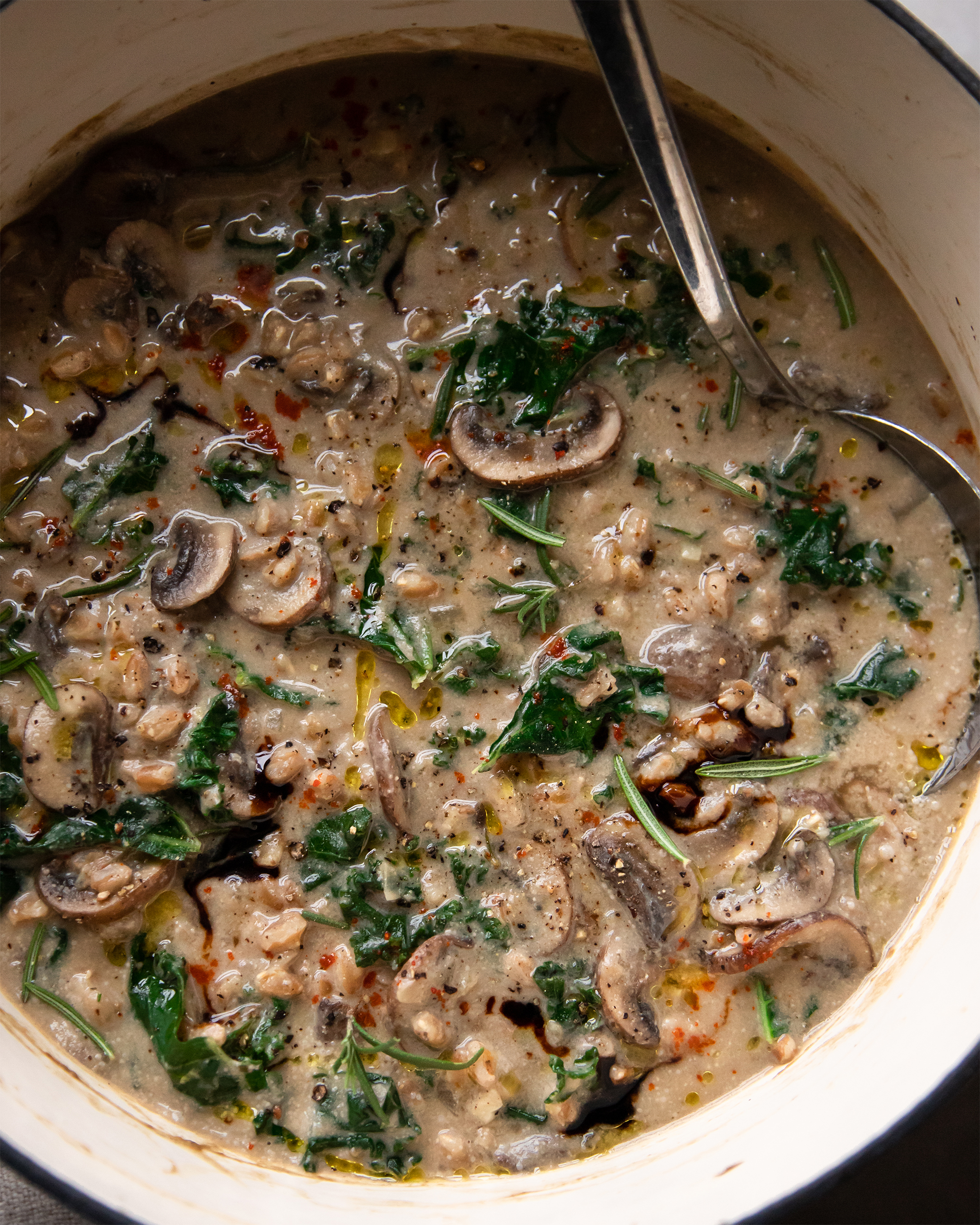 AN up close, overhead shot of creamy vegan mushroom stew with kale and farro. The soup is a golden beige colour and is inside a white Dutch oven pot.