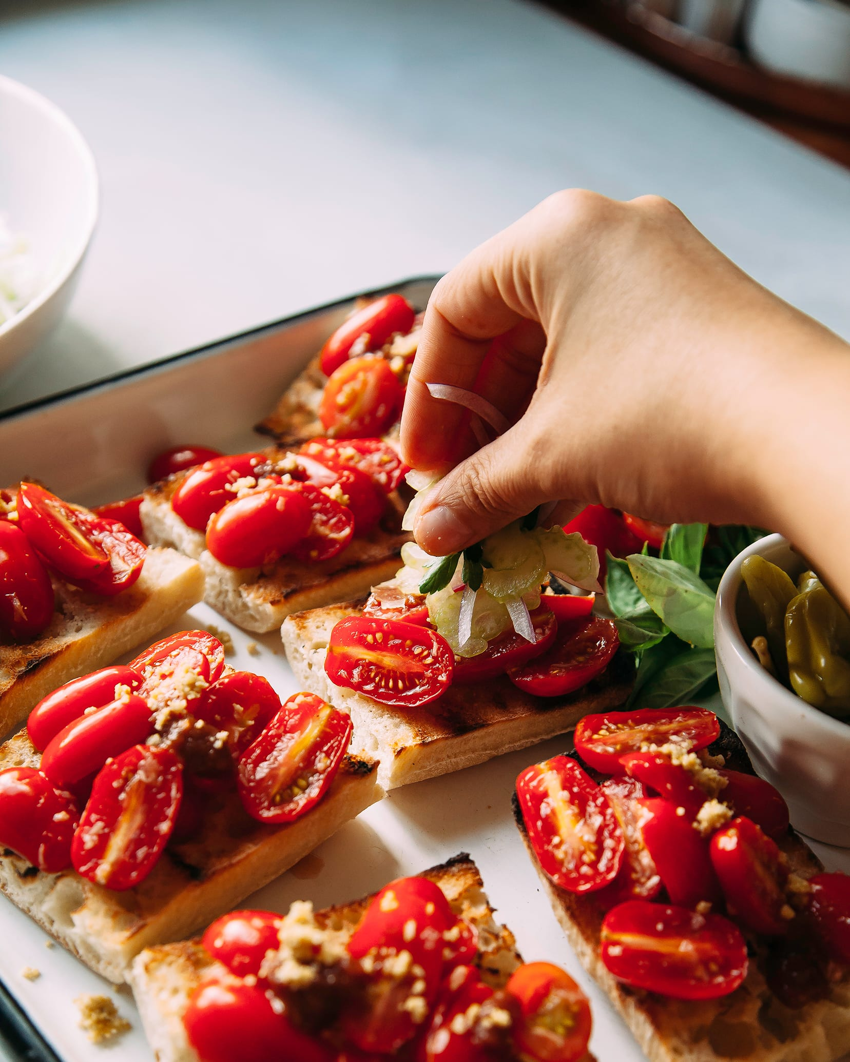 A hand is putting garnishes on top of Bloody Mary bruschetta.