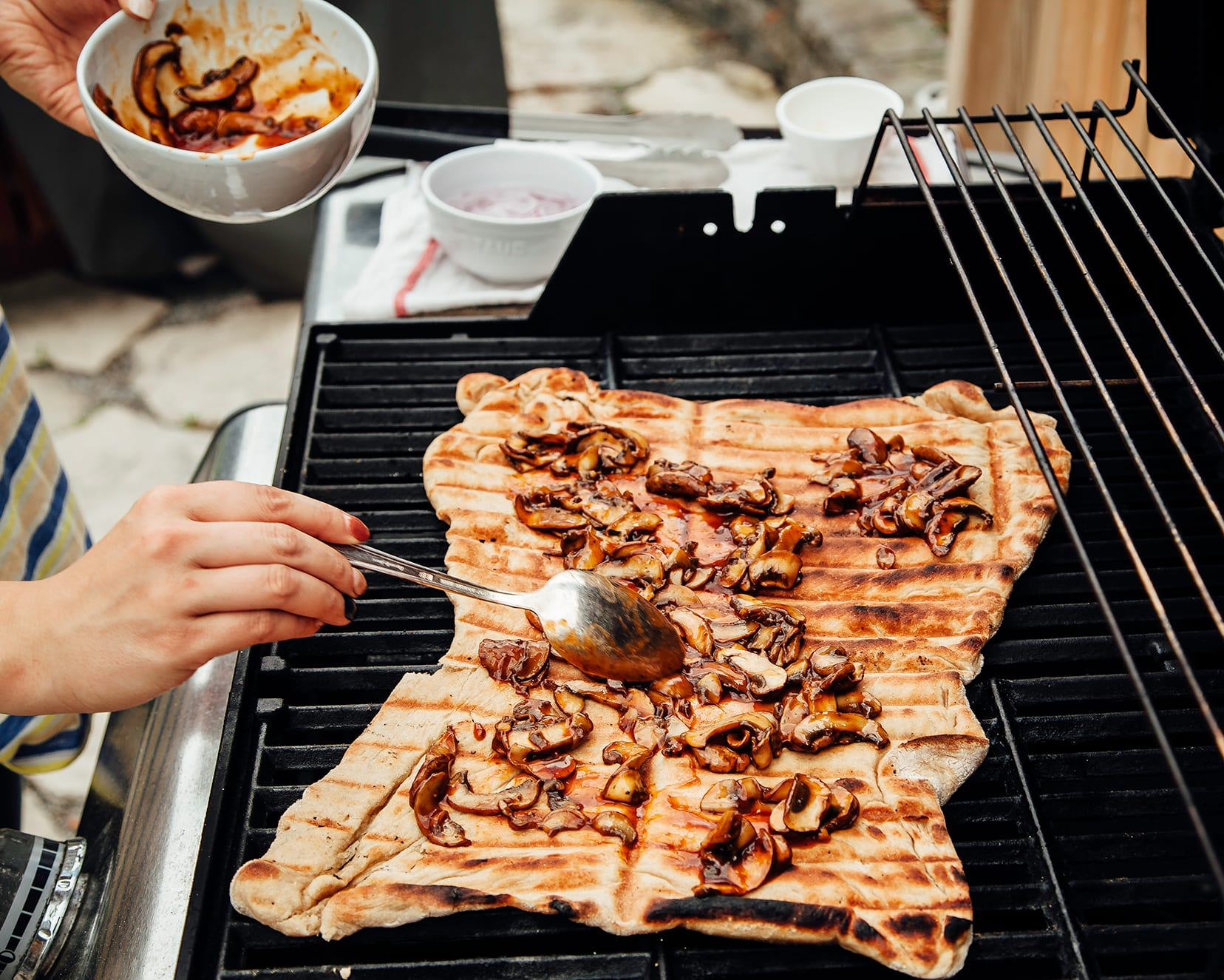 A hand is spooning saucy mushrooms onto a flatbread on an outdoor grill.