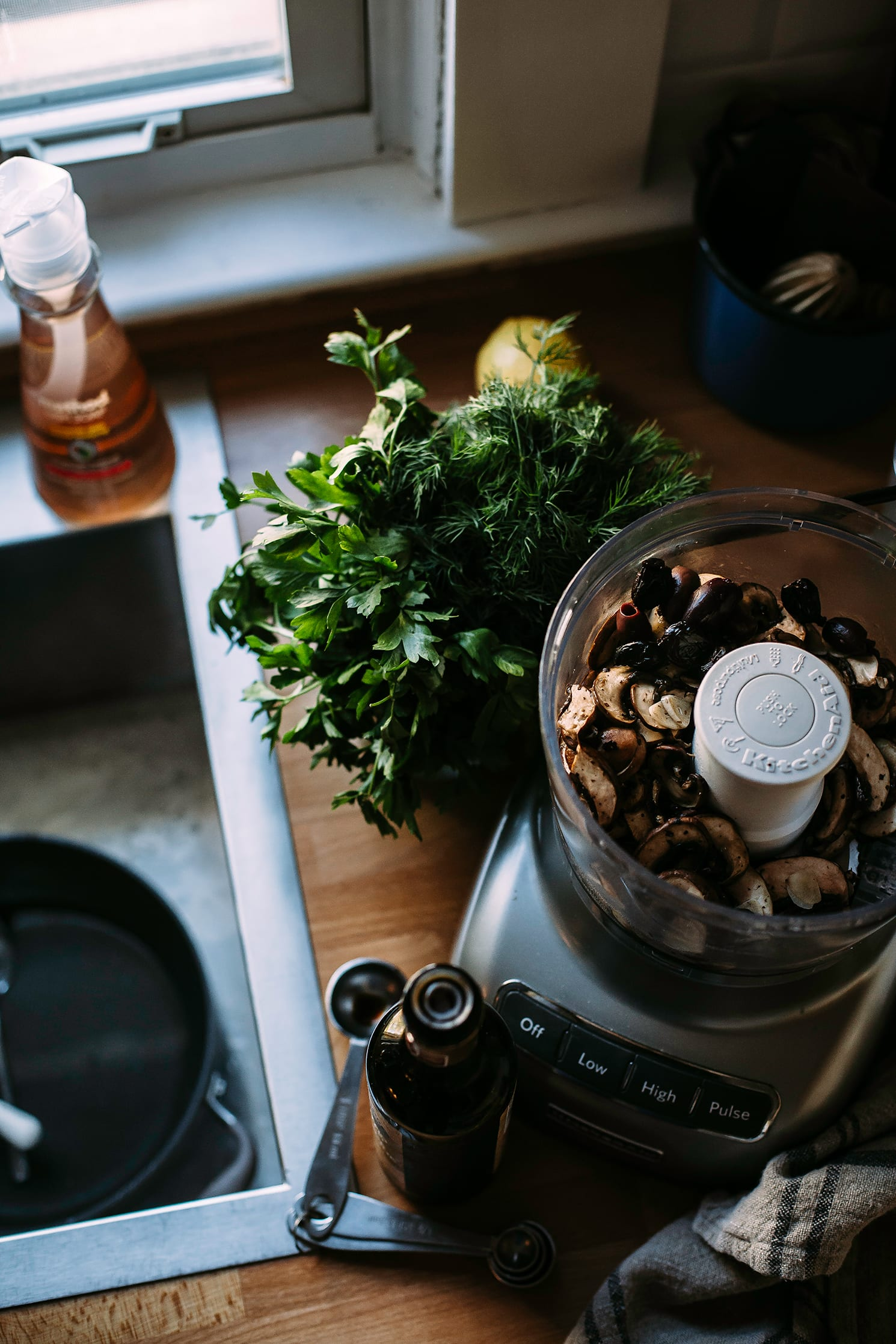 Image shows cooked mushrooms in the bowl of a food processor with a bouquet of fresh herbs nearby.