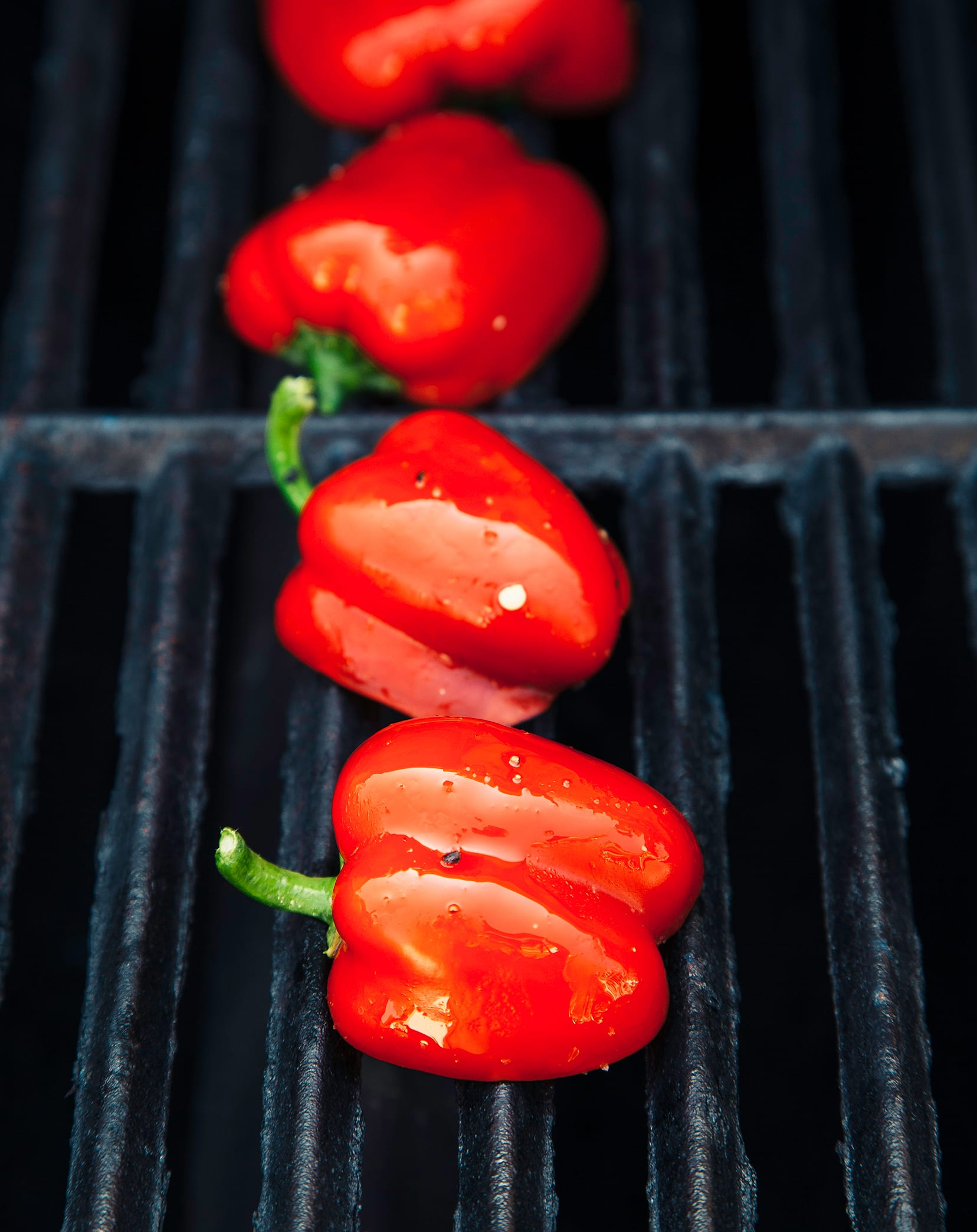 Halved mini red peppers on a grill.