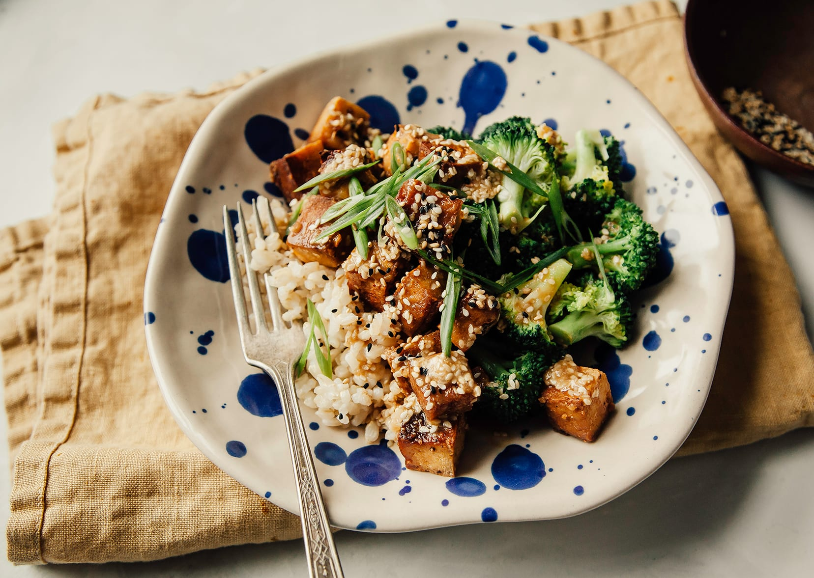 Overhead shot of crispy sesame garlic tofu in a bowl with some brown rice and steamed broccoli