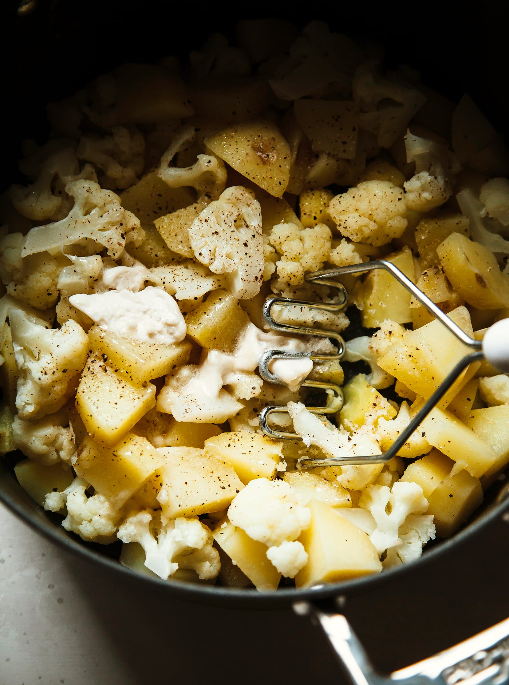 Cooked potatoes and cauliflower are being mashed with vegan butter.