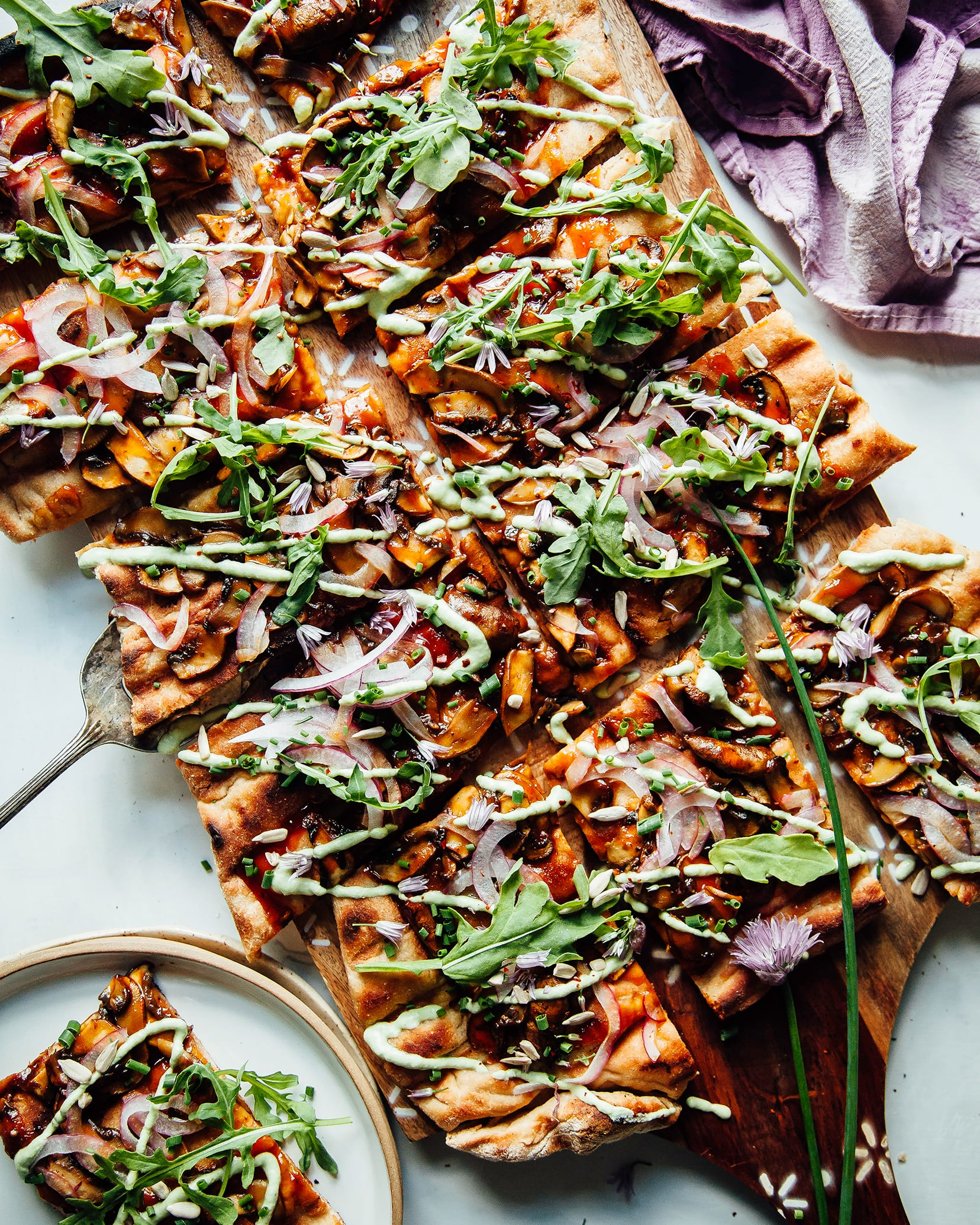 An overhead shot of a grilled flatbread with mushrooms, red onions, BBQ sauce, and a drizzle of a pale green chive sauce. The flatbread is cut into square pieces and is garnished with fresh arugula.