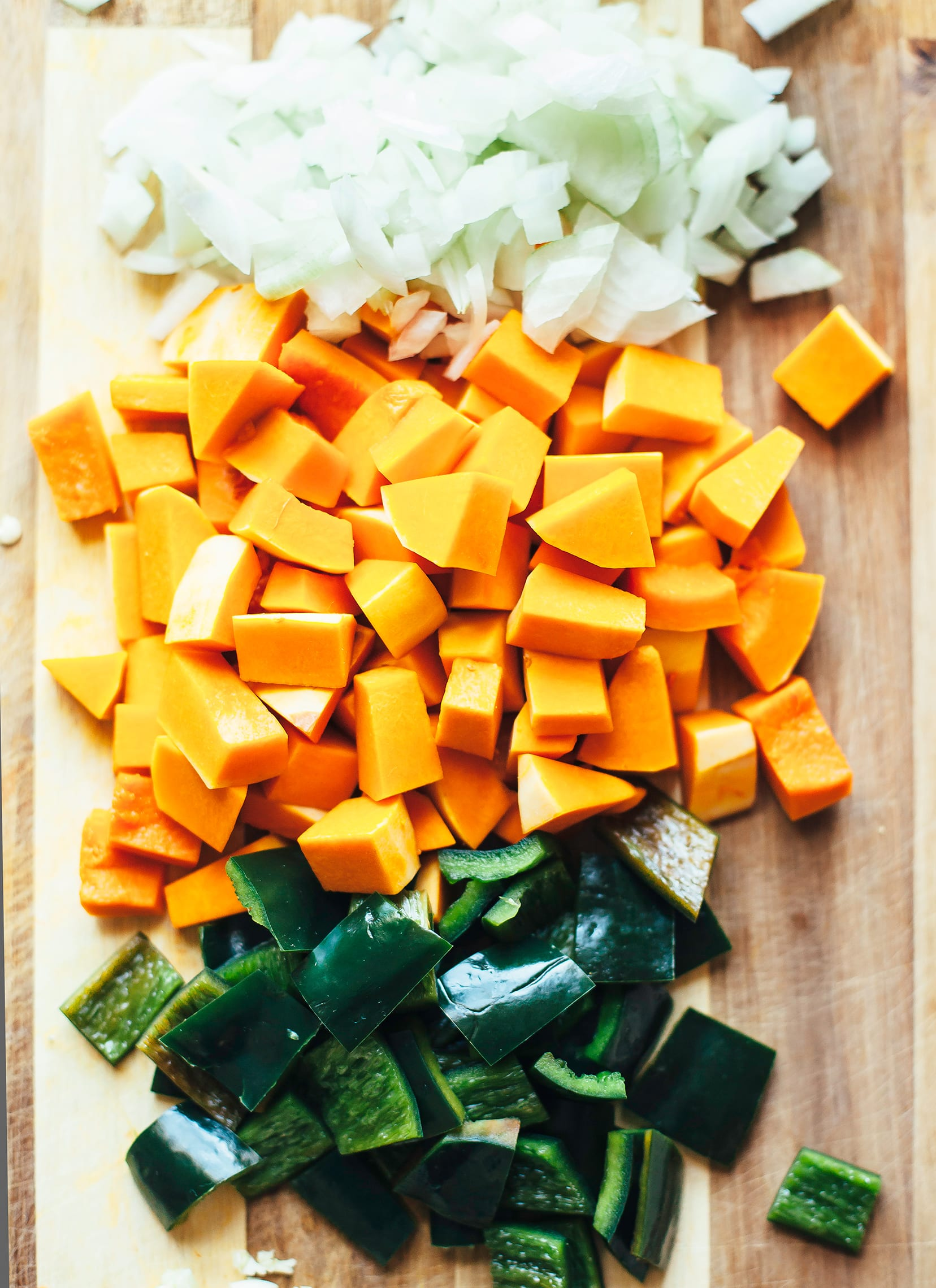 An overhead shot of chopped squash, onions and poblano pepper.