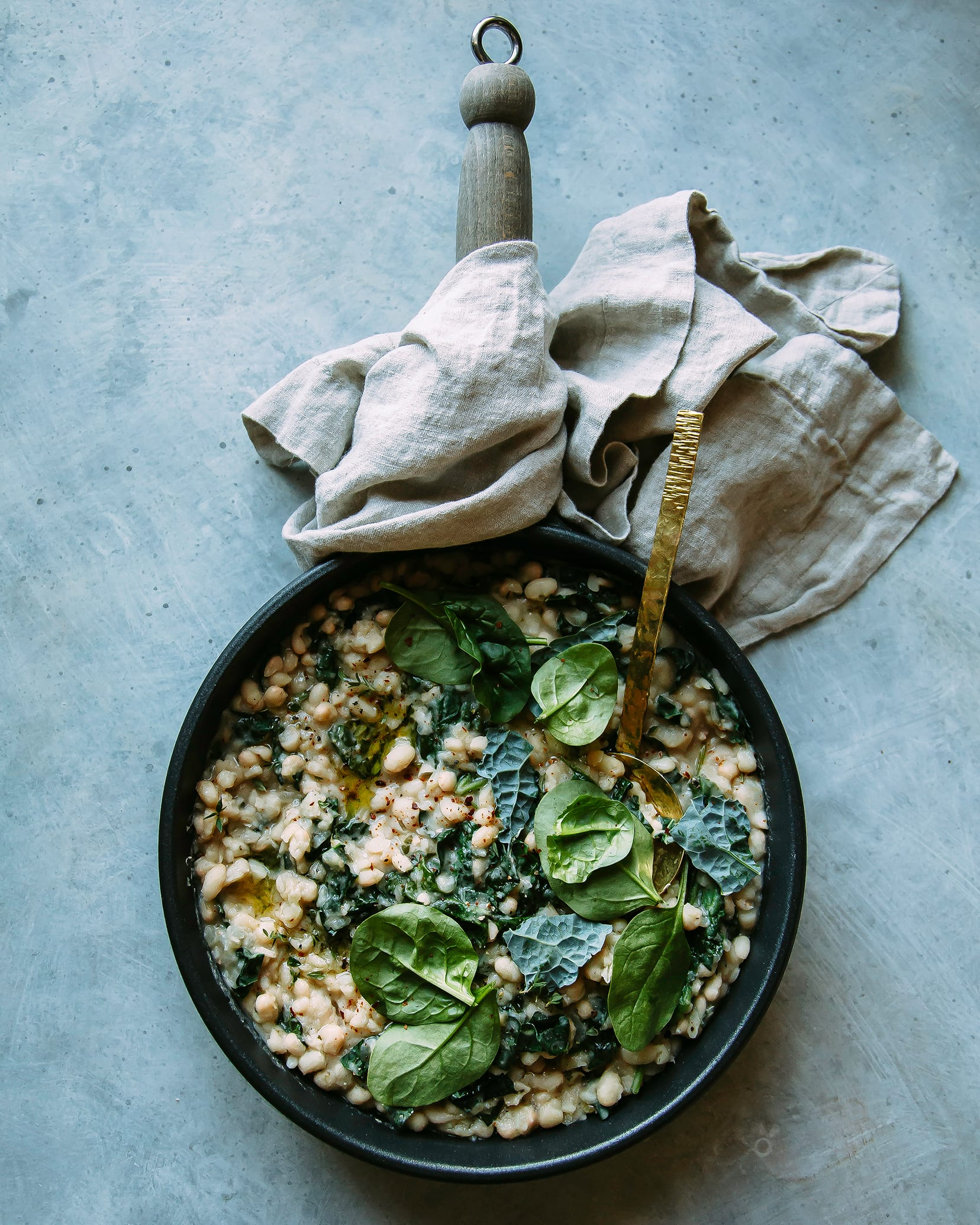 Overhead shot of creamy white beans with greens in a skillet.