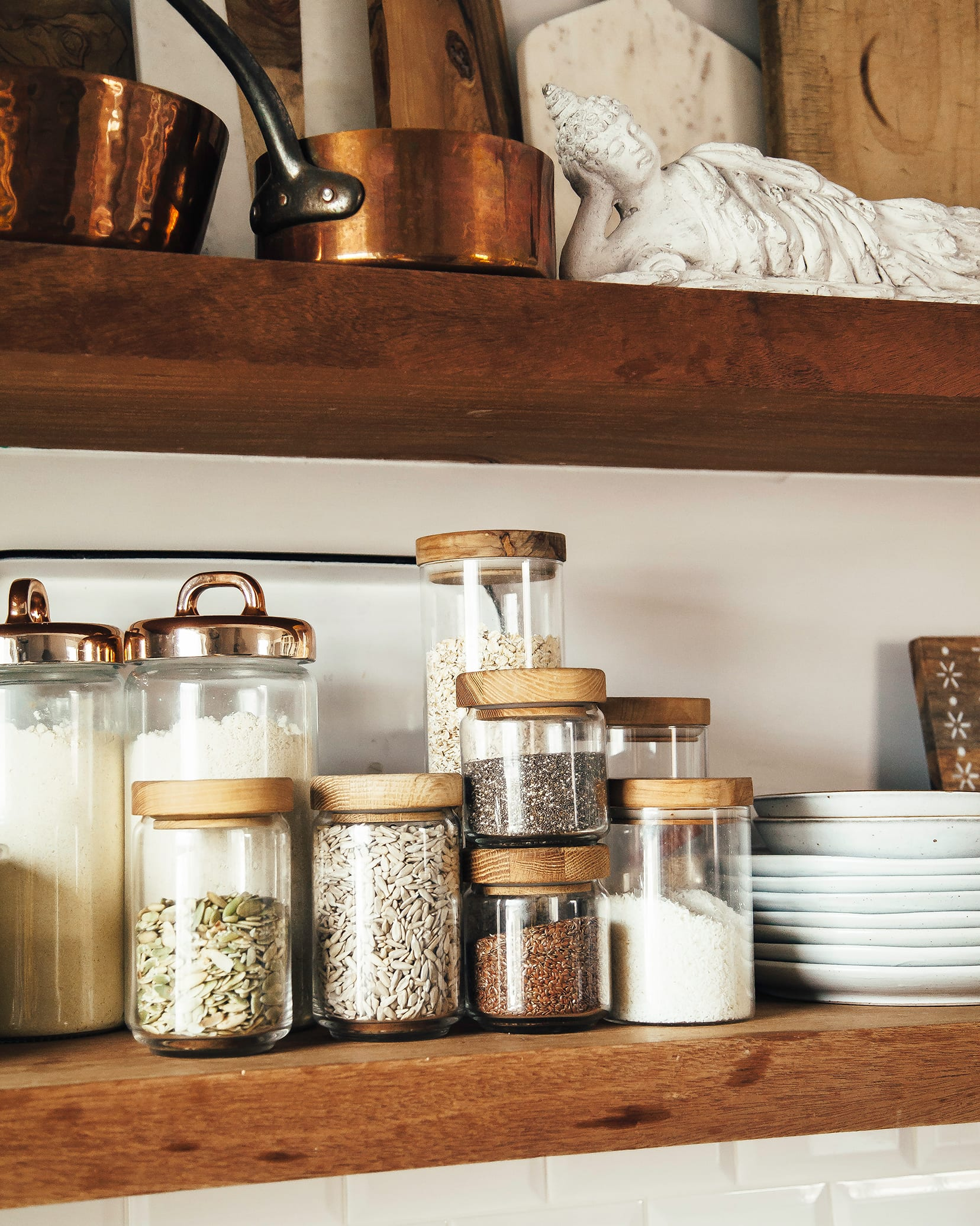 The image shows open shelving in a kitchen with a focus on storage jars filled with pantry staples like oats, seeds, and shredded coconut.