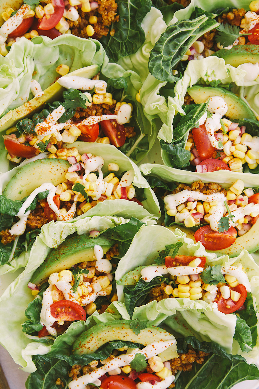 "An up close, overhead shot of raw vegan tacos. The tacos are encased in green cabbage and chard leaves and filled with spiced walnut ""meat,"" corn salsa, chopped cherry tomatoes, slices of avocado, and drizzles of cashew ""sour cream."""