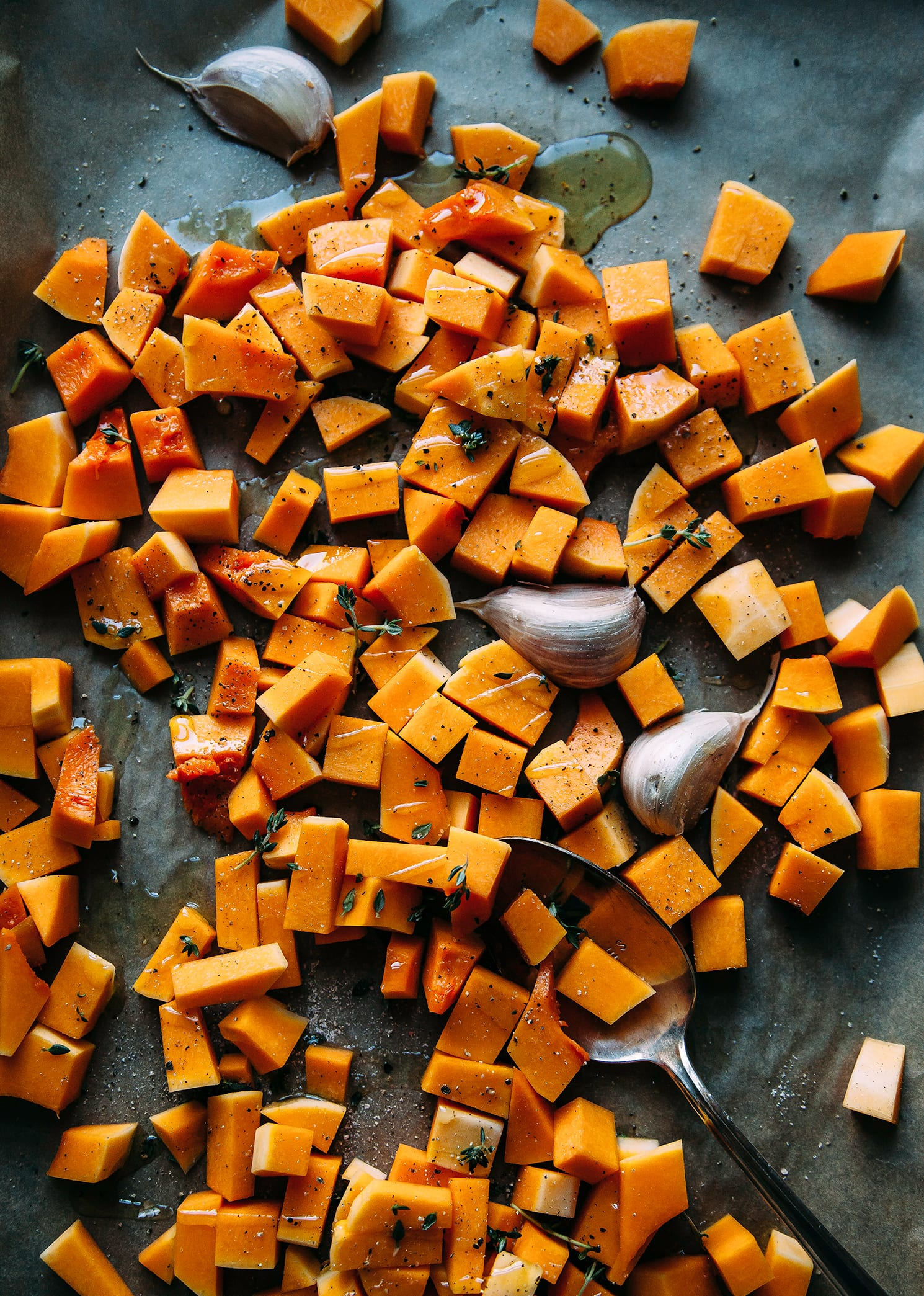 Overhead shot of butternut squash cubes and garlic cloves on a baking sheet before roasting.