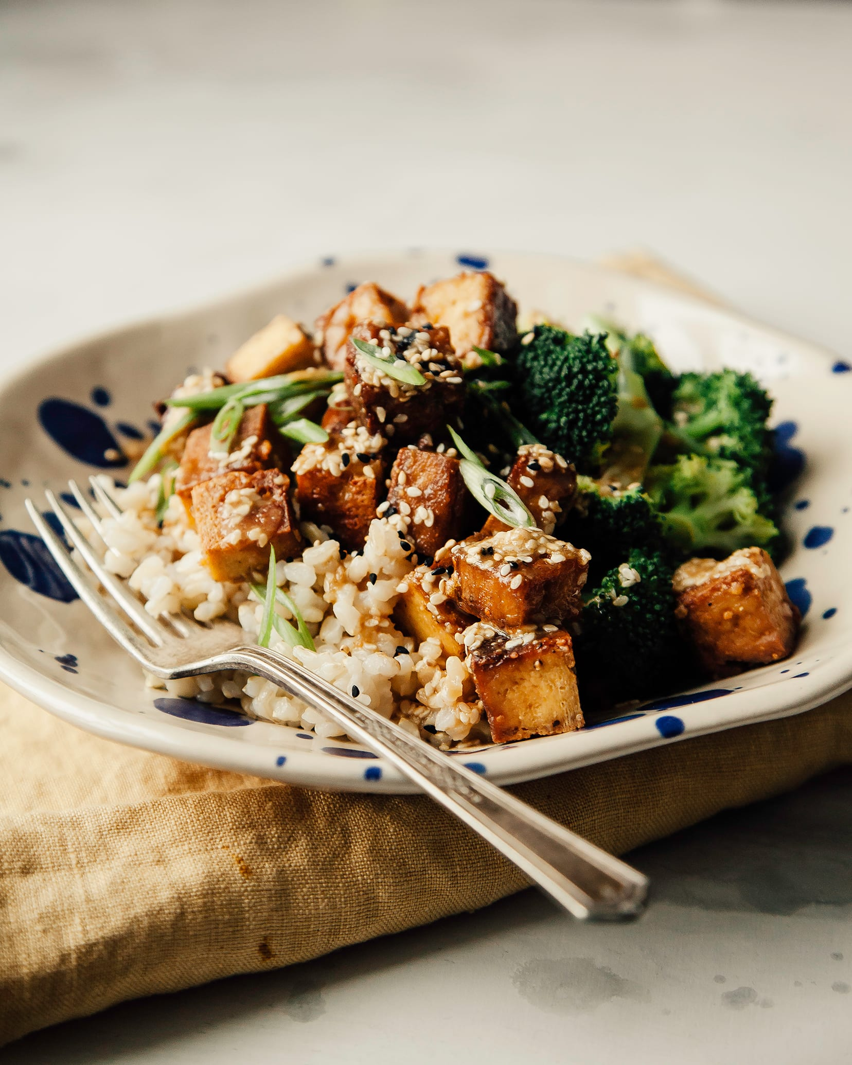Side angle shot of crispy sesame garlic tofu in a bowl with some brown rice and steamed broccoli