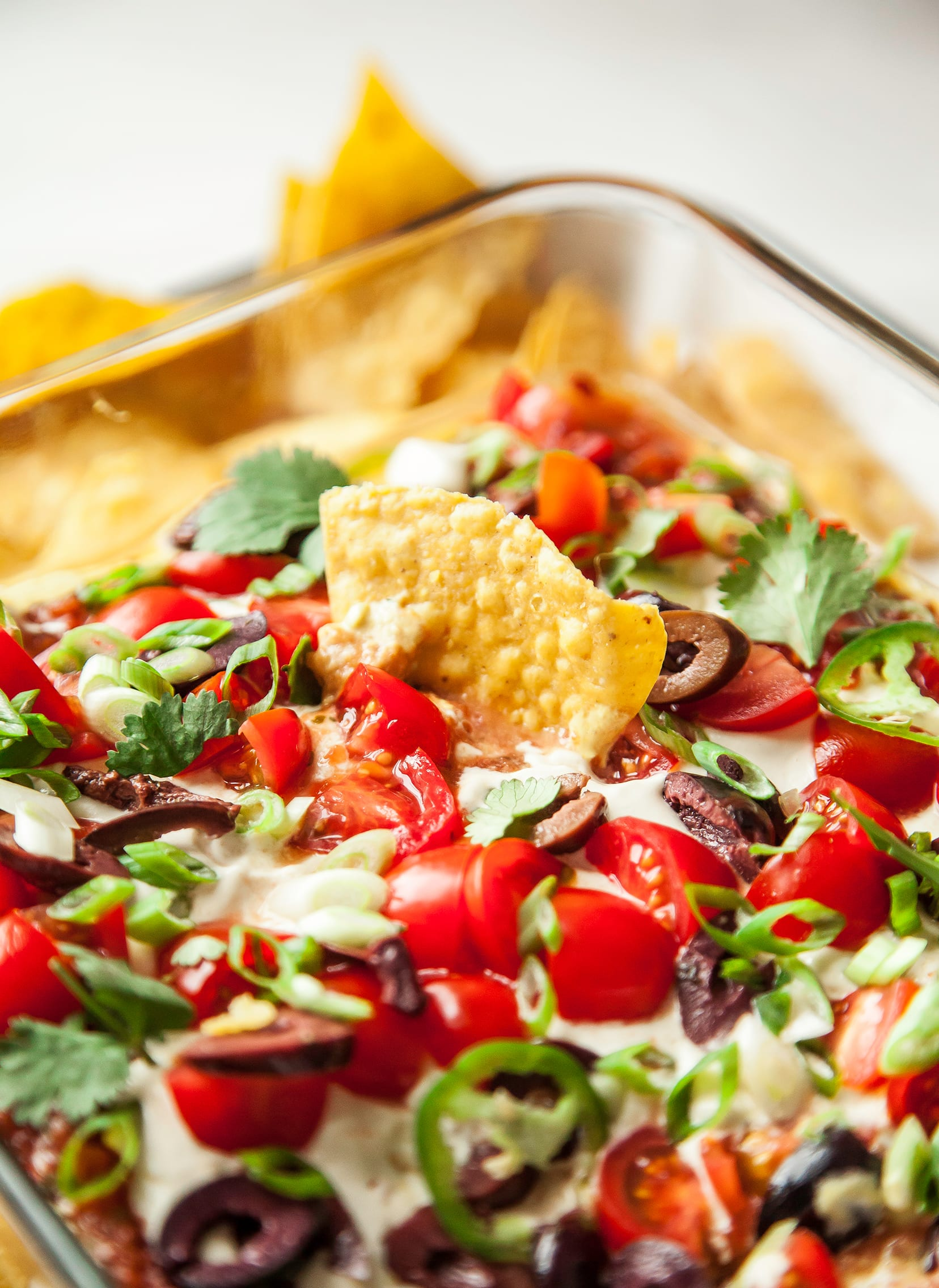 An overhead shot of a vegan seven layer dip with chips.