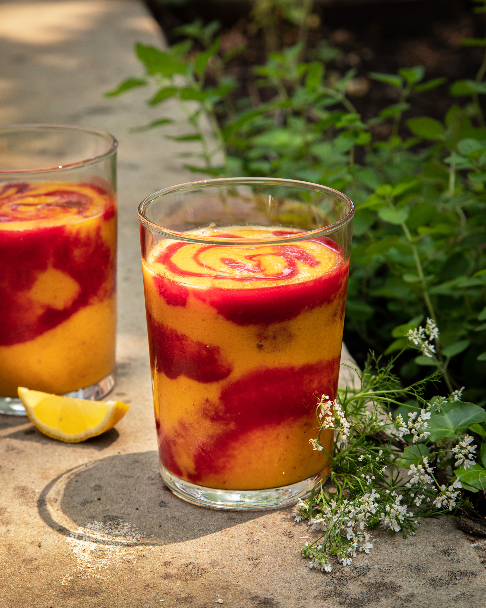 A head on shot of a swirled orange and magenta smoothie in a clear glass. The smoothie is on a concrete background with cilantro flowers nearby.