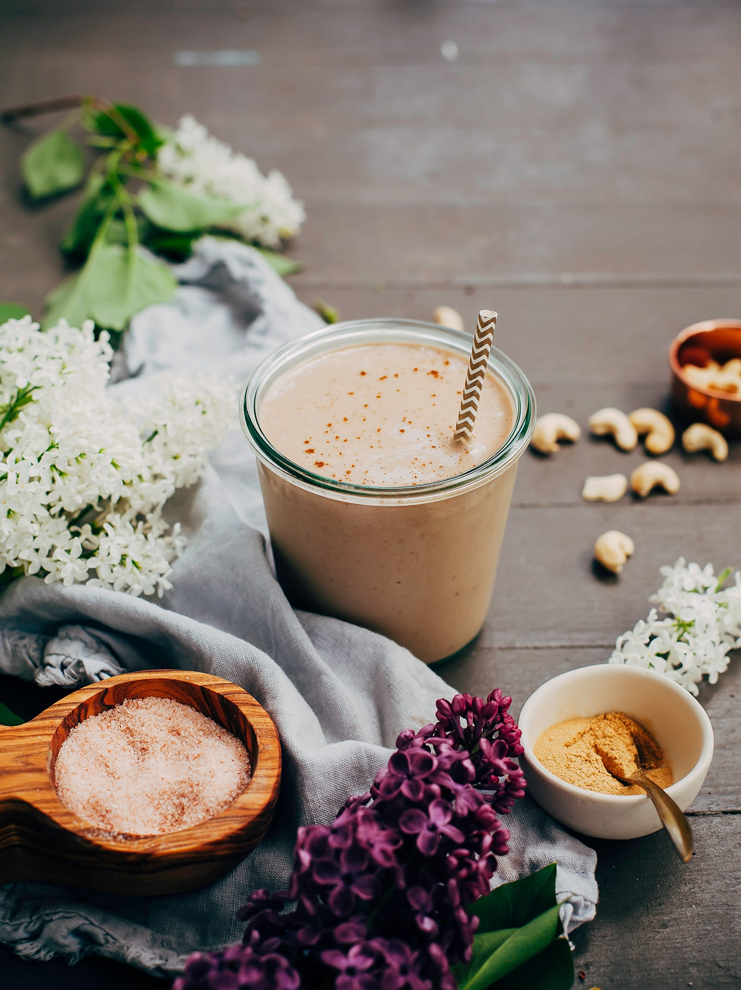 A head on shot of a maca caramel frap with some lilac flowers, a pinch bowl of salt, and raw cashews nearby.