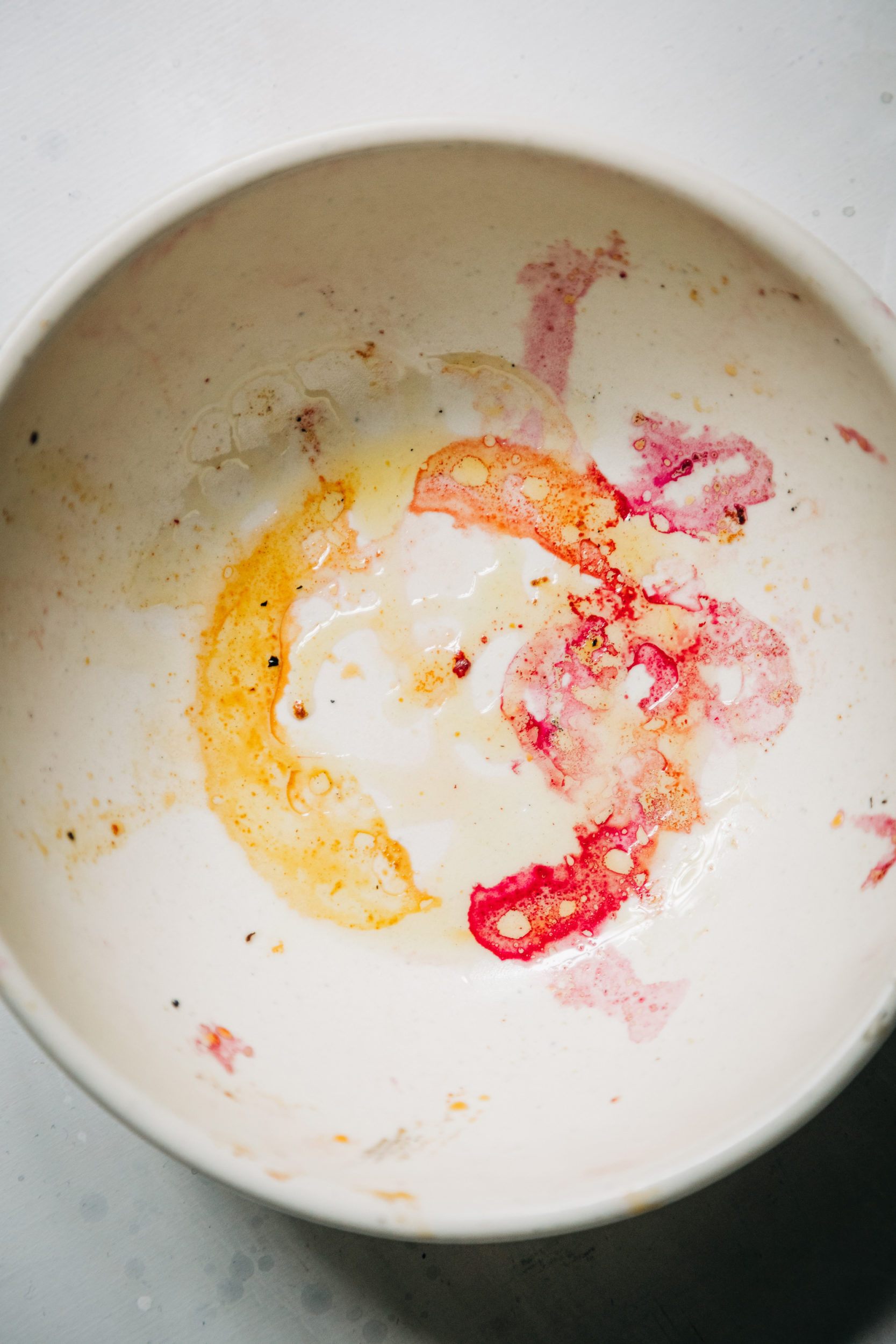 An overhead shot of pink and yellow beet stains in the bottom of a white bowl.