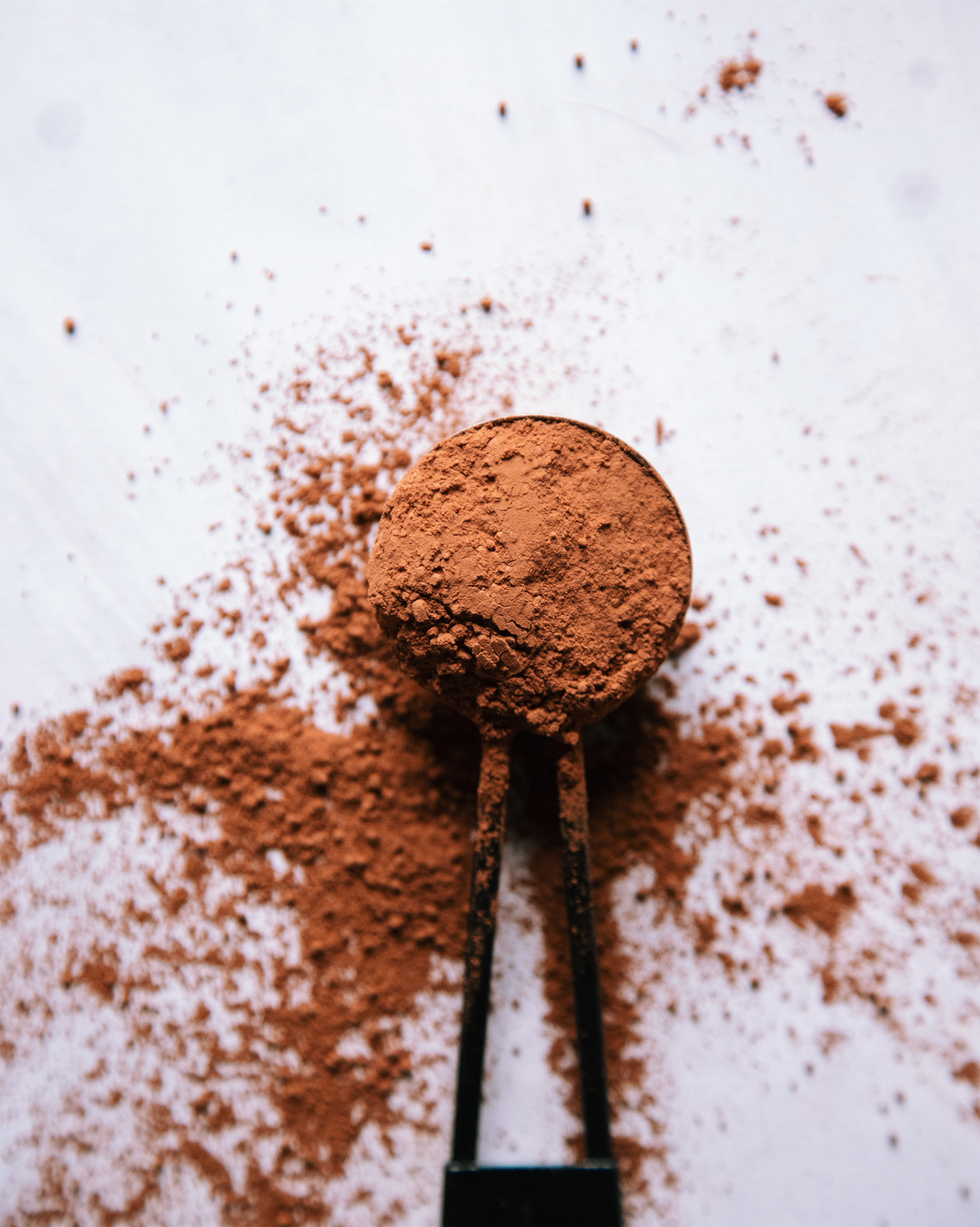 An overhead shot of a black measuring spoon filled with cacao powder on a white background. The cacao is spilled out all around the spoon.