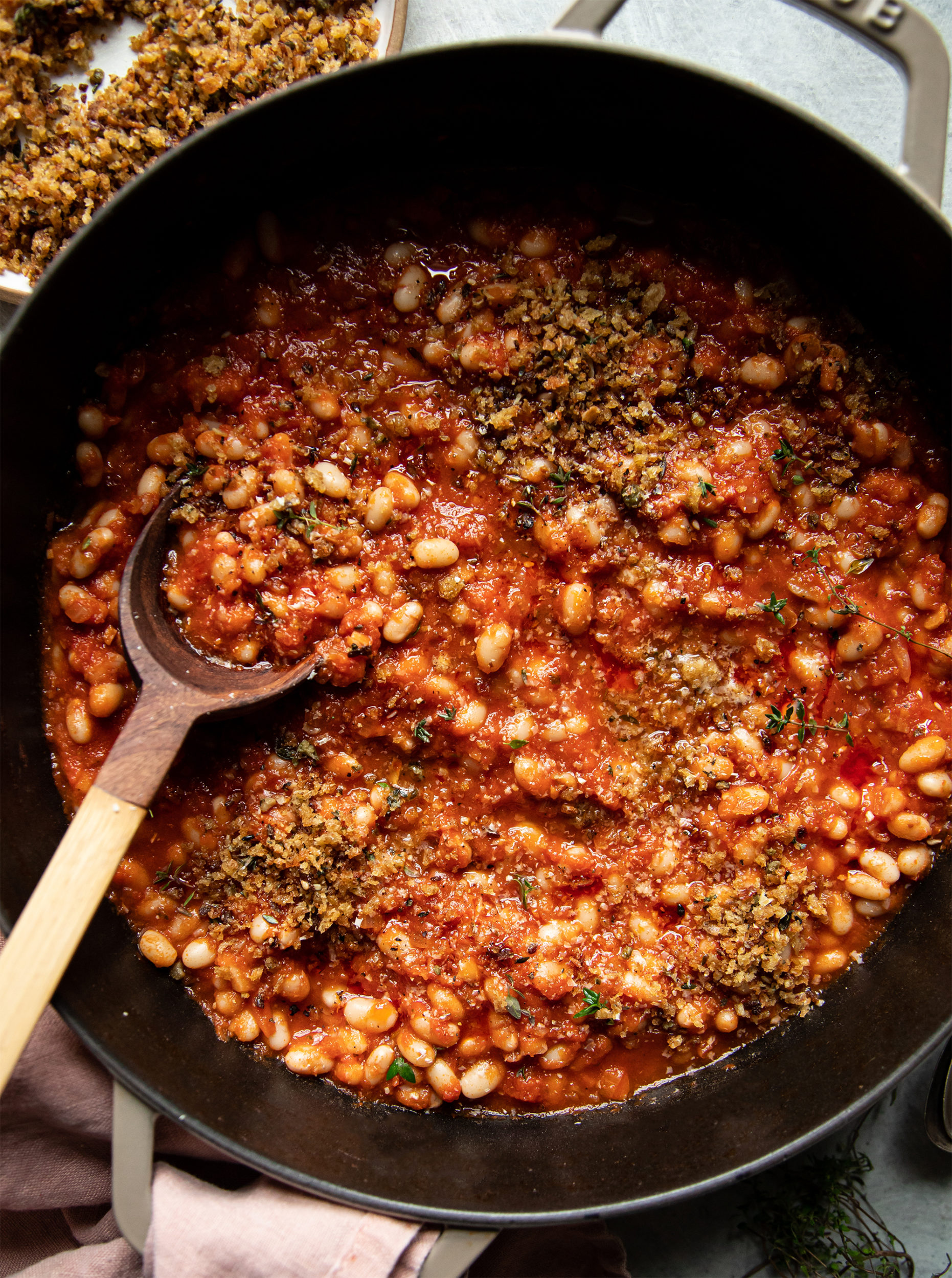 An overhead shot of jammy sun dried tomato white beans in a beige braiser-style pot. The white beans are garnished with crispy cakes breadcrumbs and thyme leaves. There is a wooden spoon sticking out of the pot.