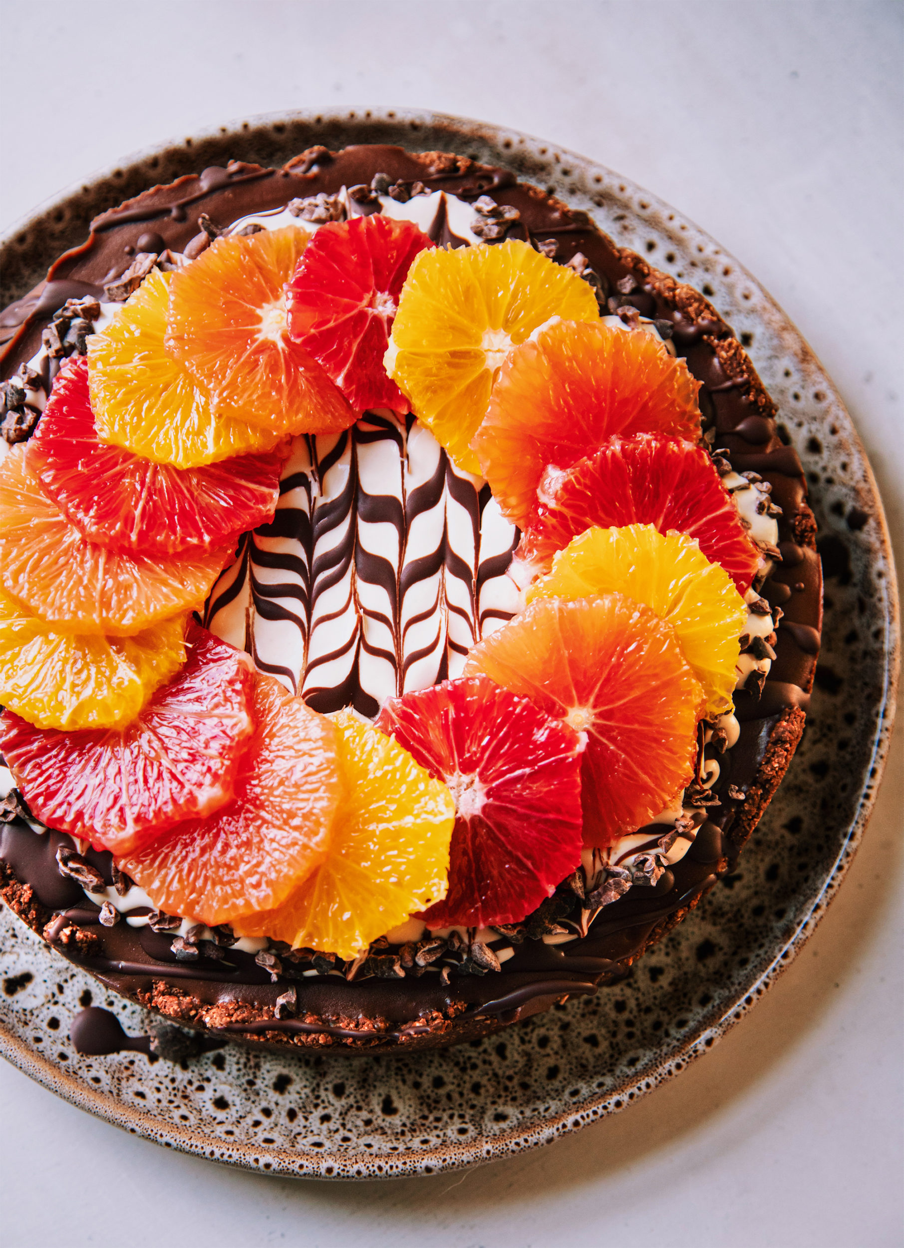 An overhead shot of a vegan chocolate orange cheesecake on a white background. The top of the cheesecake has a wreath or different coloured orange slices on top of a white cashew cream and melted chocolate marble design. To the side is a pink linen napkin, a paring knife and a vintage silver serving utensil. Part of a roundup of vegan holiday recipes.