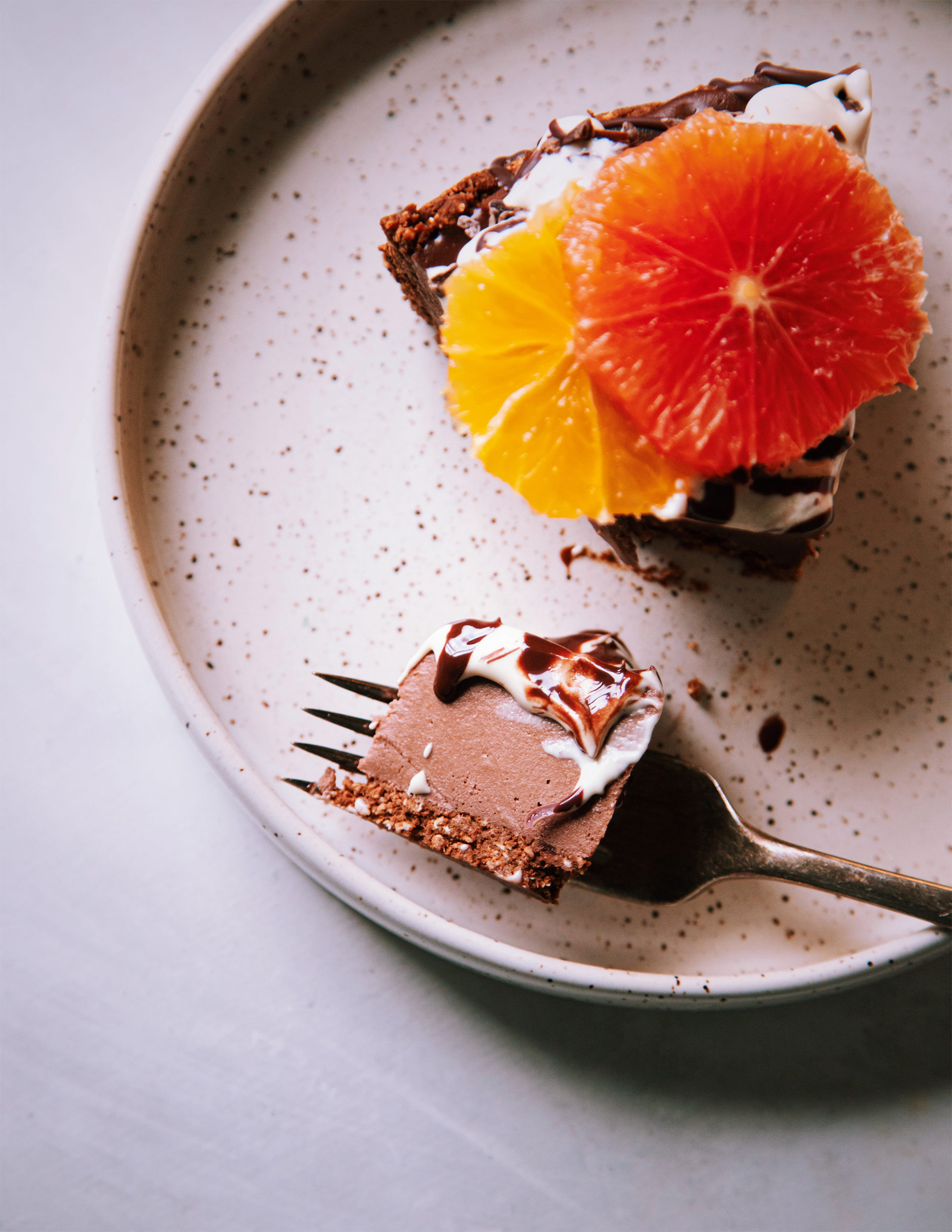 An up close, overhead shot of a slice of chocolate cheesecake with a forkful nearby on a white speckled plate.