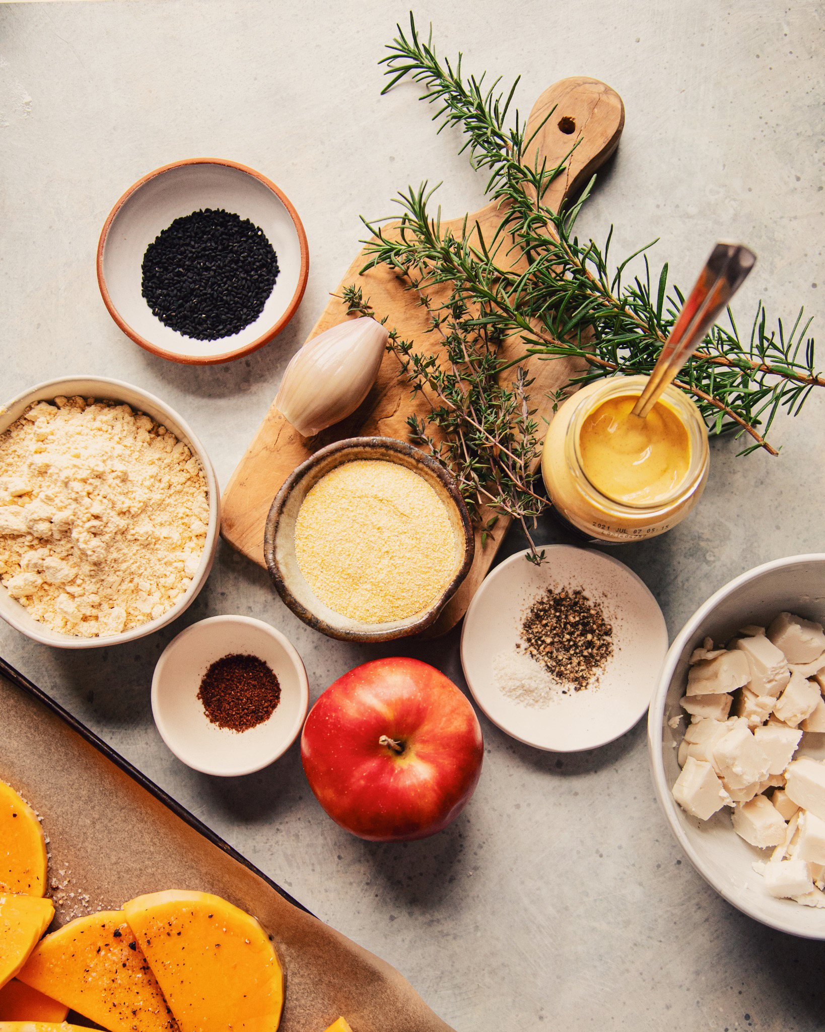 An overhead view of the ingredients including: rosemary, thyme, squash, chickpea flour in a bowl, cornmeal in a bowl, salt, pepper and apple, shallot and a small bowl of black cumin seeds.  All on a gray background.